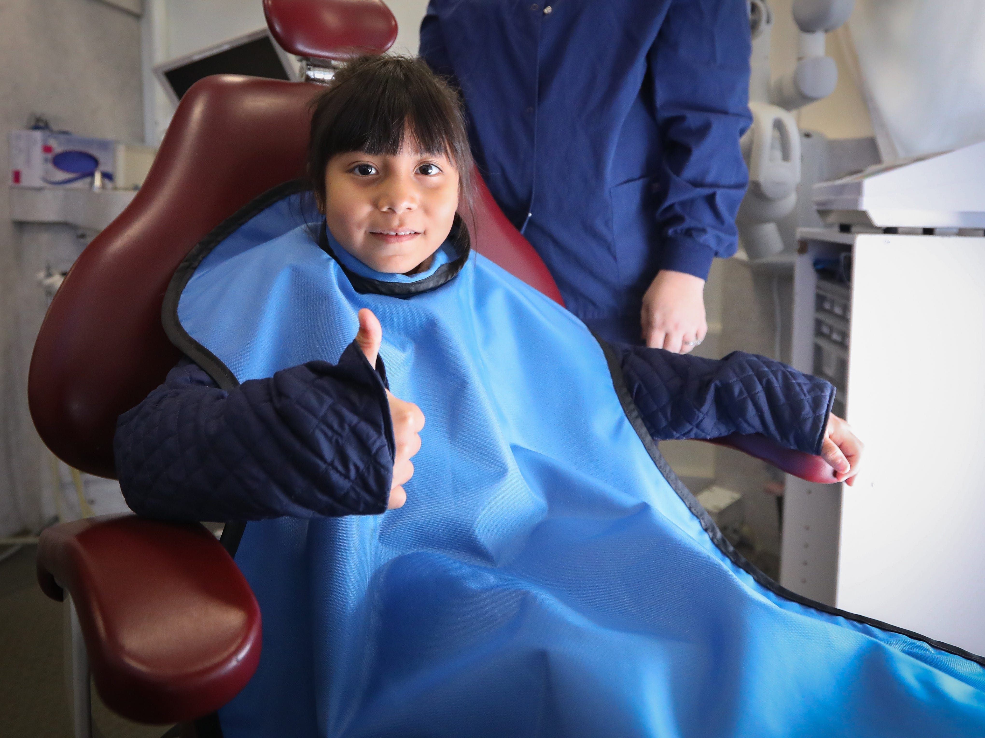 "Angela Alvarez, a Karen Acres kindergartner, gives a thumbs up prior to getting her teeth inspected in the Dental Connections mobile unit at Karen Acres Elementary School on Nov. 15, 2018 in Urbandale, Iowa. ""Dental Connections is a mobile unit that provides basic dental check-ups for students."
