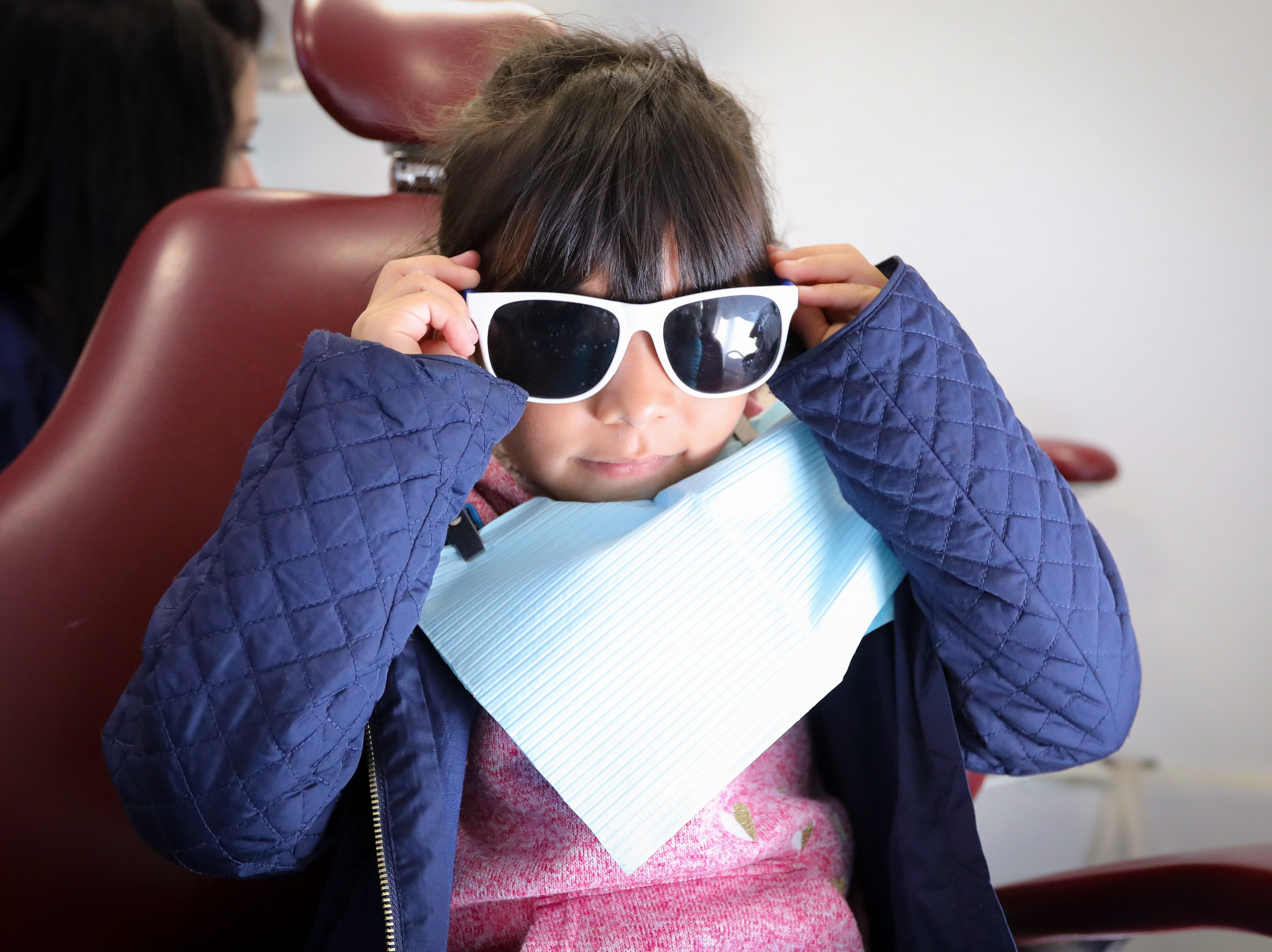 Angela Alvarez, a Karen Acres kindergartner, puts on her safety sunglasses prior to having her teeth inspected in the Dental Connections mobile unit at Karen Acres Elementary School on Nov. 15, 2018 in Urbandale, Iowa. Dental Connections is a mobile unit that provides basic dental check-ups for students.