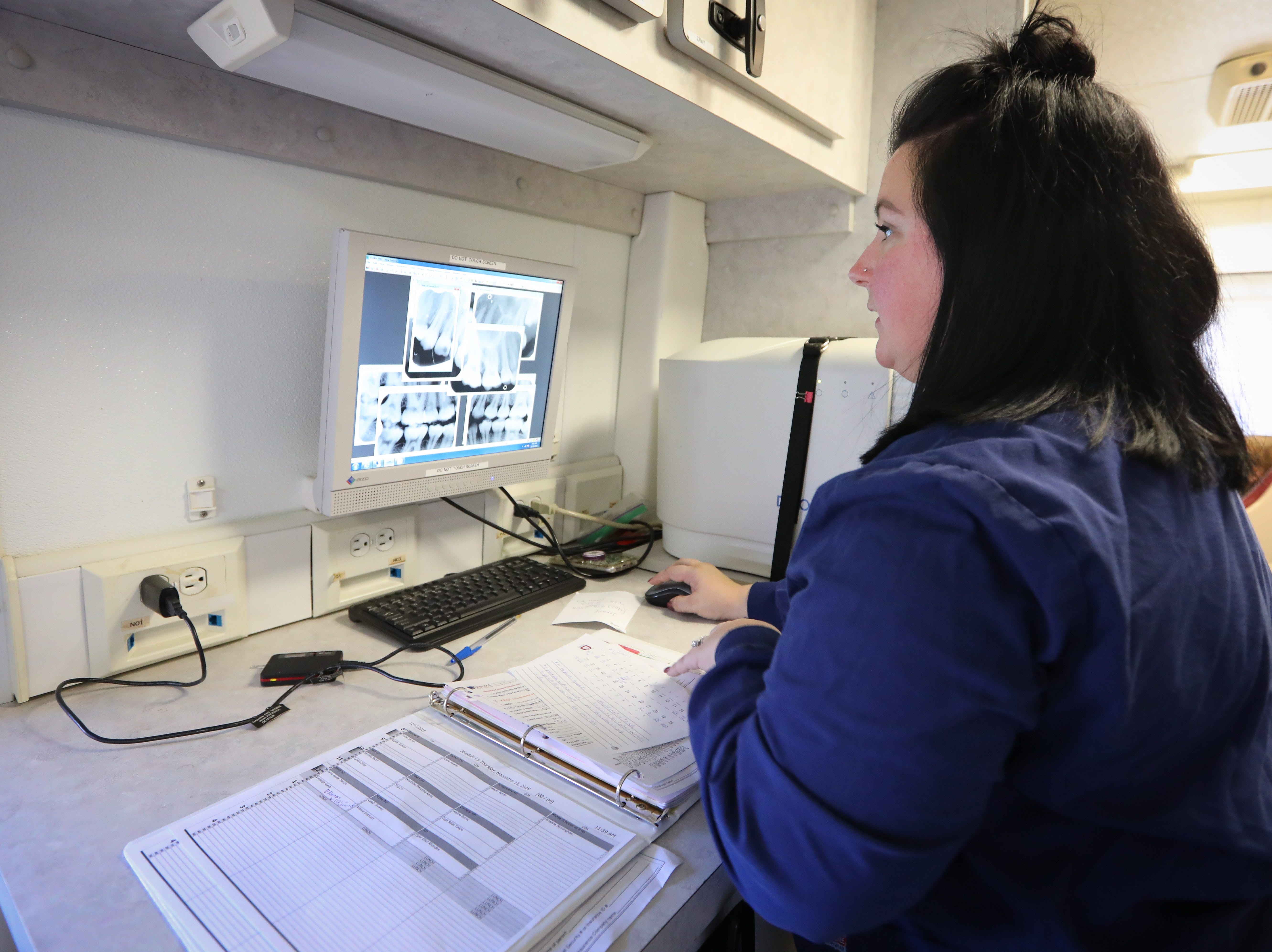 Hygienist Carissa Thompson, 37, of Des Moines, inspects the x-ray results inside the Dental Connections mobile unit in the Dental Connections mobile unit at Karen Acres Elementary School on Nov. 15, 2018 in Urbandale, Iowa. Dental Connections is a mobile unit that provides basic dental check-ups for students.