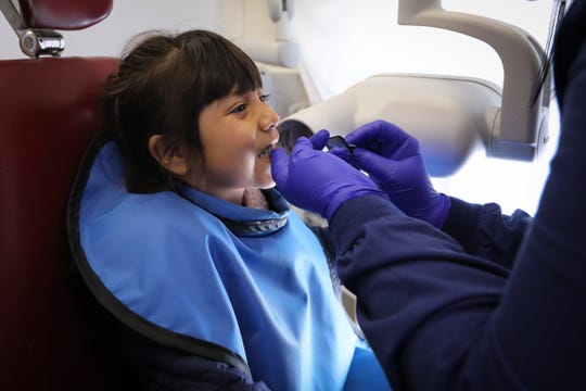 A kindergartner prepares for X-rays in the Dental Connections mobile unit at Karen Acres Elementary School, Urbandale, in this Nov. 15, 2018, file photo.