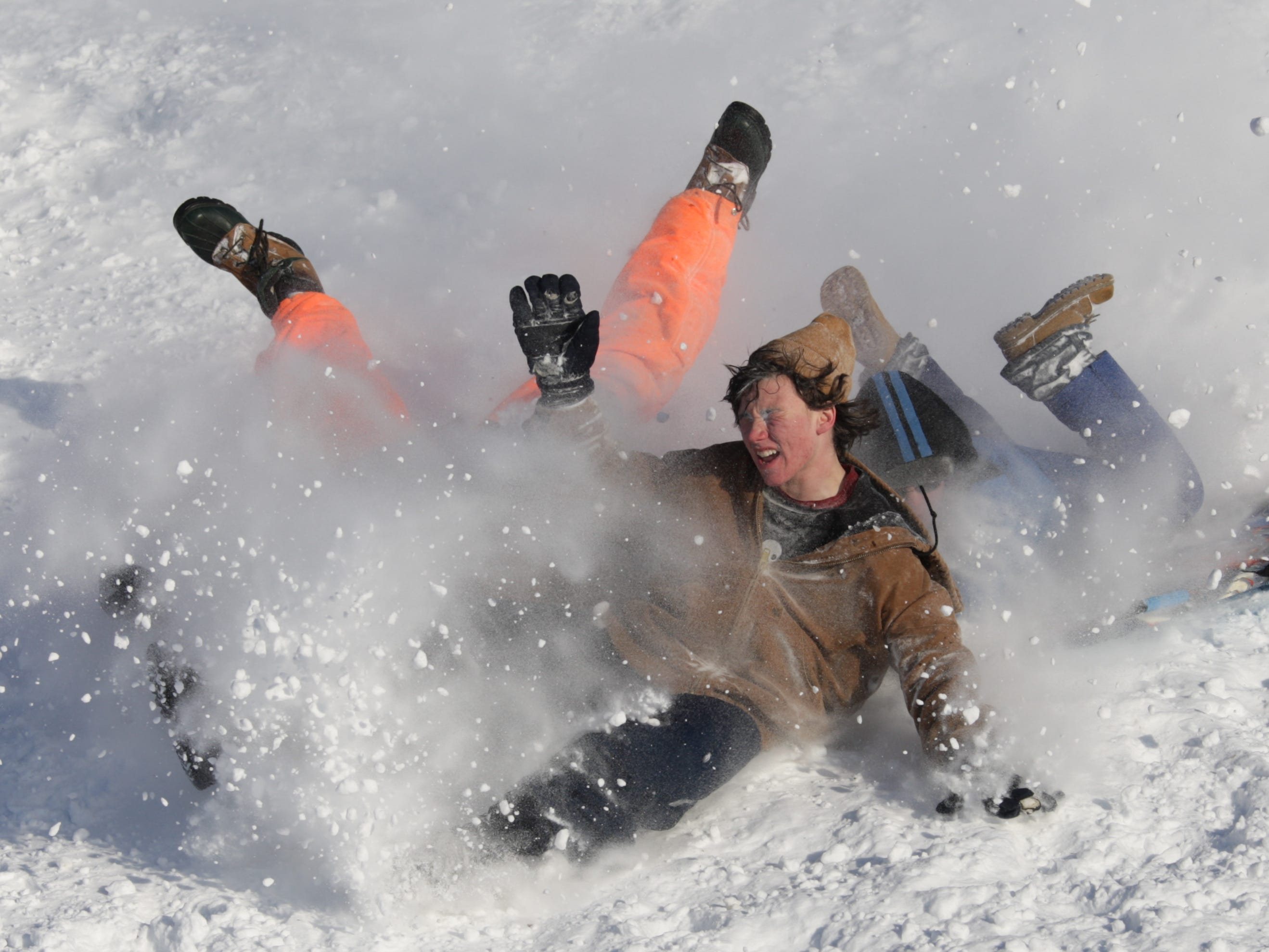 Dustin Petty, 14, visible, Richard Smith, 15, orange legs, and Monty Miller, 12, blue legs, all of Des Moines, wipe out as they sled near the State Capitol building on Dec. 10, 2009.