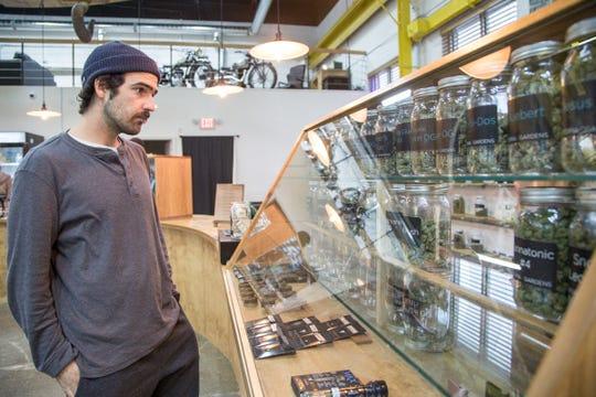 Trevor Newman of Detroit, an employee of Utopia Gardens medical marijuana dispensary looks over product at the store in Detroit, Thursday, Nov. 15, 2018.