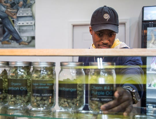 Manager Donnell Cravens looks for a product on the shelf for a customer at Utopia Gardens medical marijuana dispensary in Detroit, Thursday, Nov. 15, 2018.