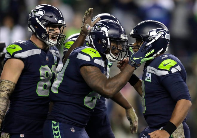 Seattle Seahawks tight end Ed Dickson, center, celebrates with quarterback Russell Wilson, right, and tight end Nick Vannett, left, after Dickson caught a pass from Wilson for a touchdown.