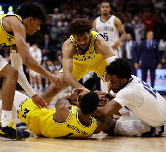 Michigan's Isaiah Livers (top), Charles Matthews (bottom) and Eli Brooks struggle for a loose ball against Villanova.