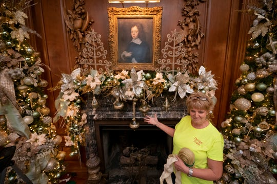 Cheryl Mast, of Lowell, shows off a mantle she decorated in the dining room of  Meadow Brook Hall.