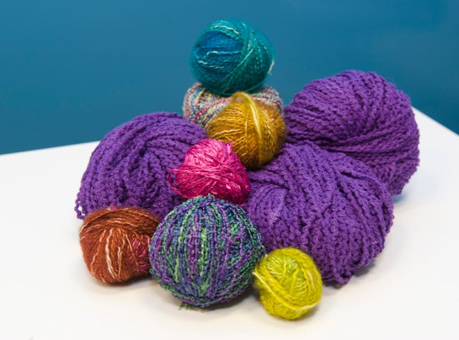 balls of yarn for a purple knitted scarf.
