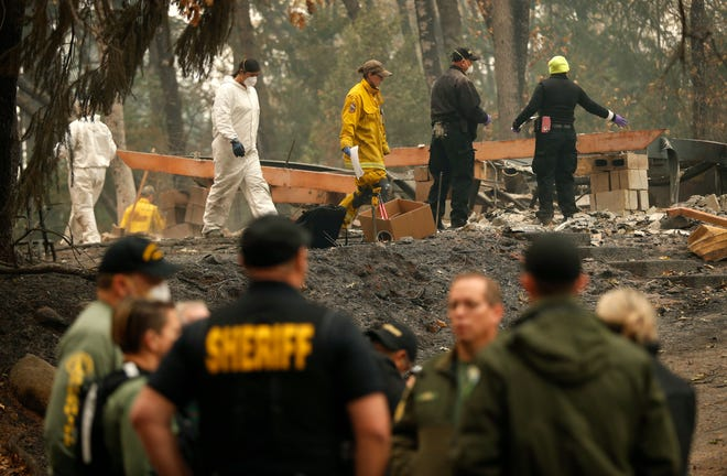 Investigators recover human remains at a home burned in the Camp Fire, Thursday, Nov. 15, 2018, in Magalia, Calif. Many of the missing in the deadly Northern California wildfire are elderly residents in Magalia, a forested town of about 11,000 north of the destroyed town of Paradise.