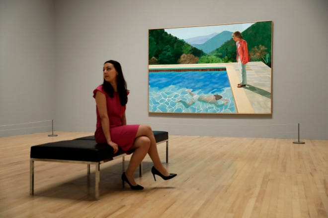 """In this Feb. 6, 2017, file photo, a Tate representative poses for photographs next to British artist David Hockney's """"Portrait of an Artist (Pool with Two Figures) during a photo call to promote the largest-ever retrospective of his work at Tate Britain gallery in London."""