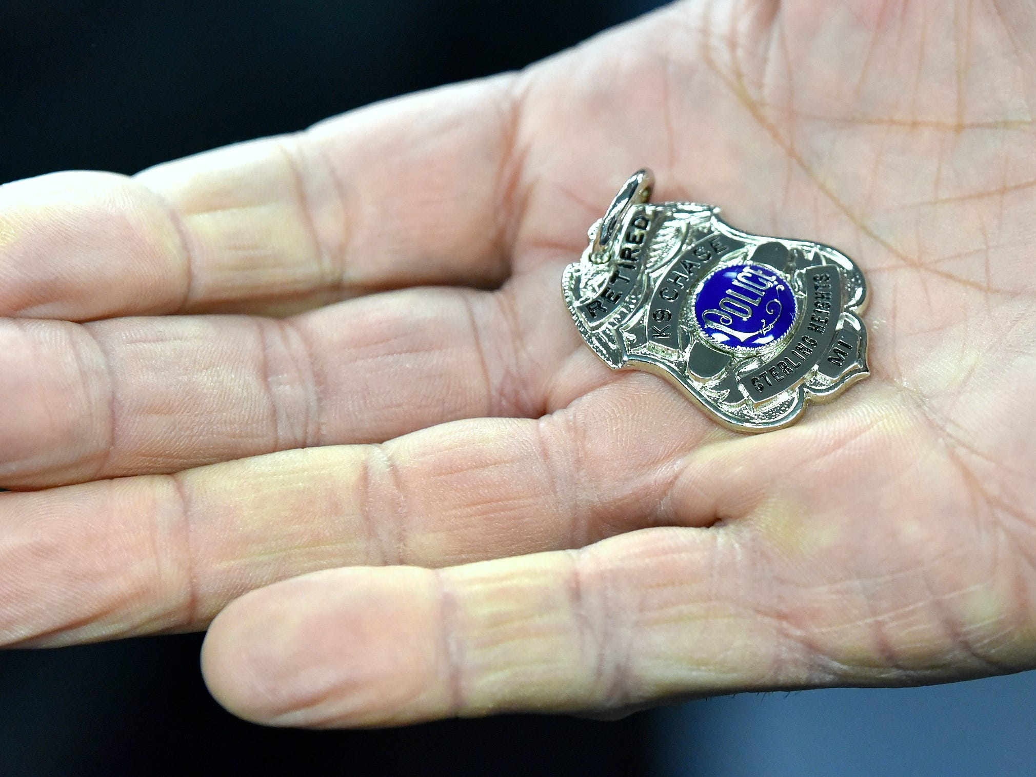 K-9 officer Rich Heins shows off the retirement badge of his dog, Chase.