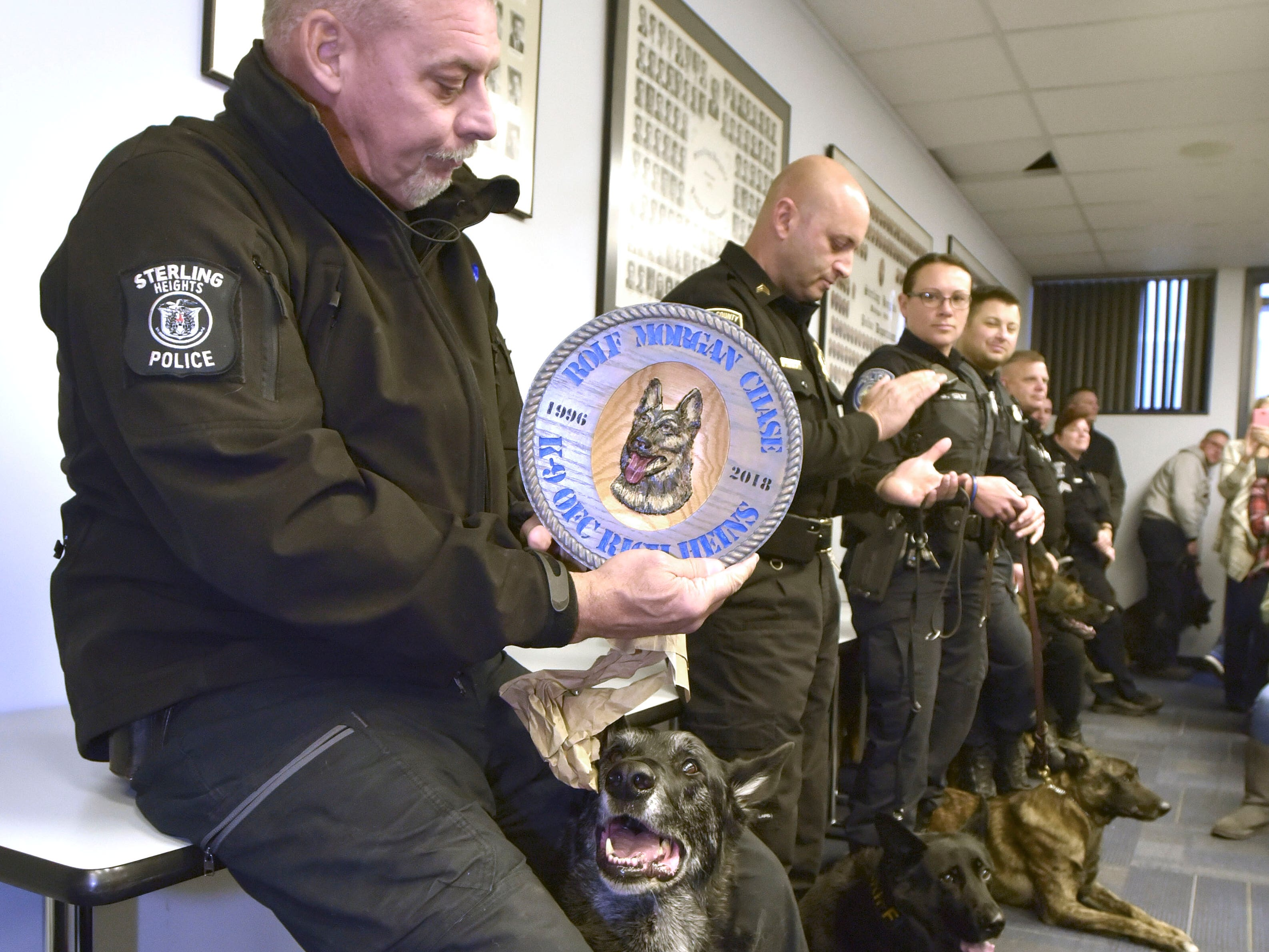 Sterling Heights Police K-9 officer Rich Heins tries to contain his emotions as he opens a present from his good friend Walt Garon, not shown, who retired from the department.