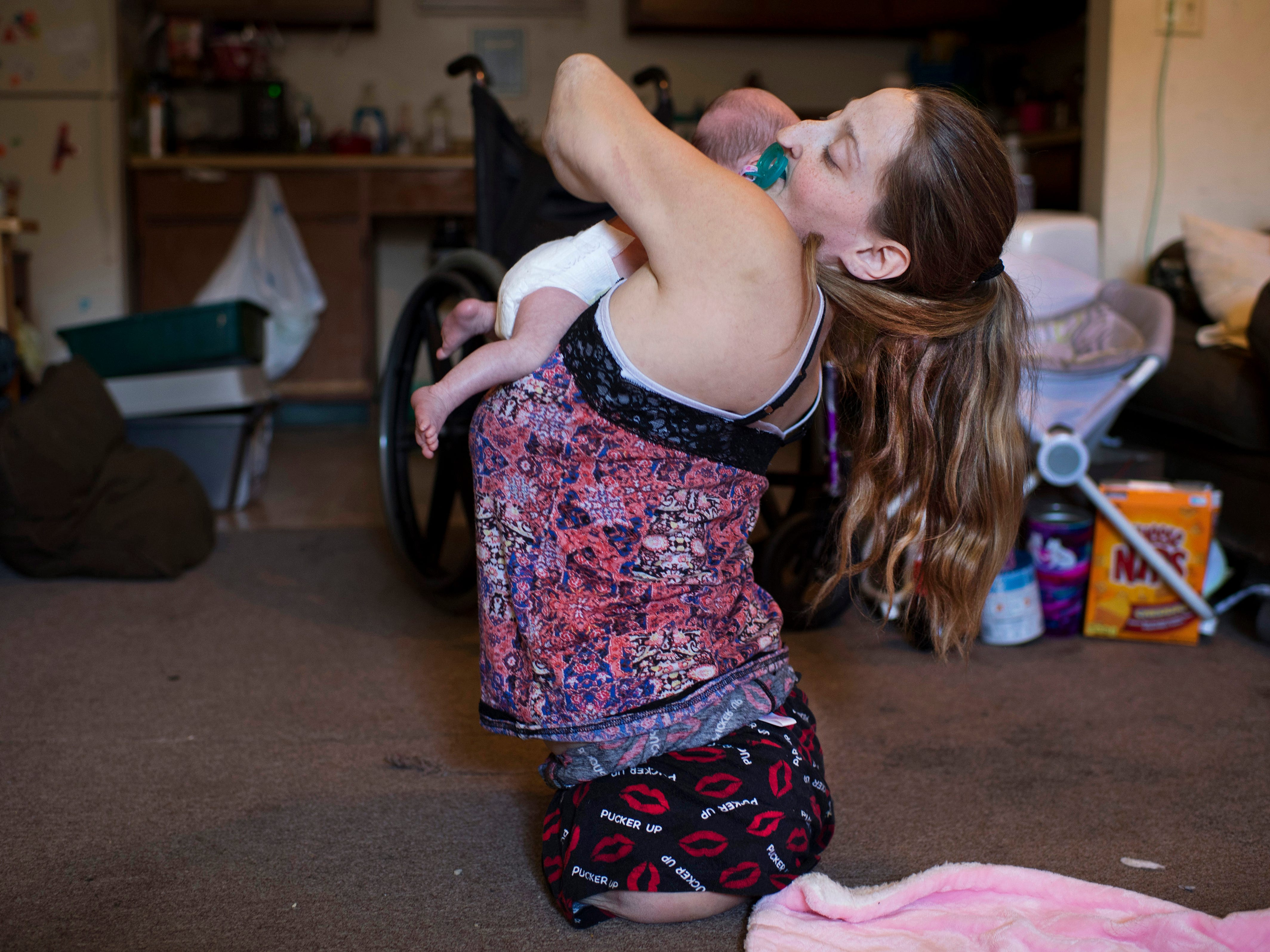 """Ashley gets a lift from her mom, Amanda Smith, after a diaper change Wednesday, Nov. 7, 2018. """"It is a little hard, but you've just got to figure stuff out and take it day by day to learn,"""" Amanda said. """"It's nothing you can learn overnight."""""""