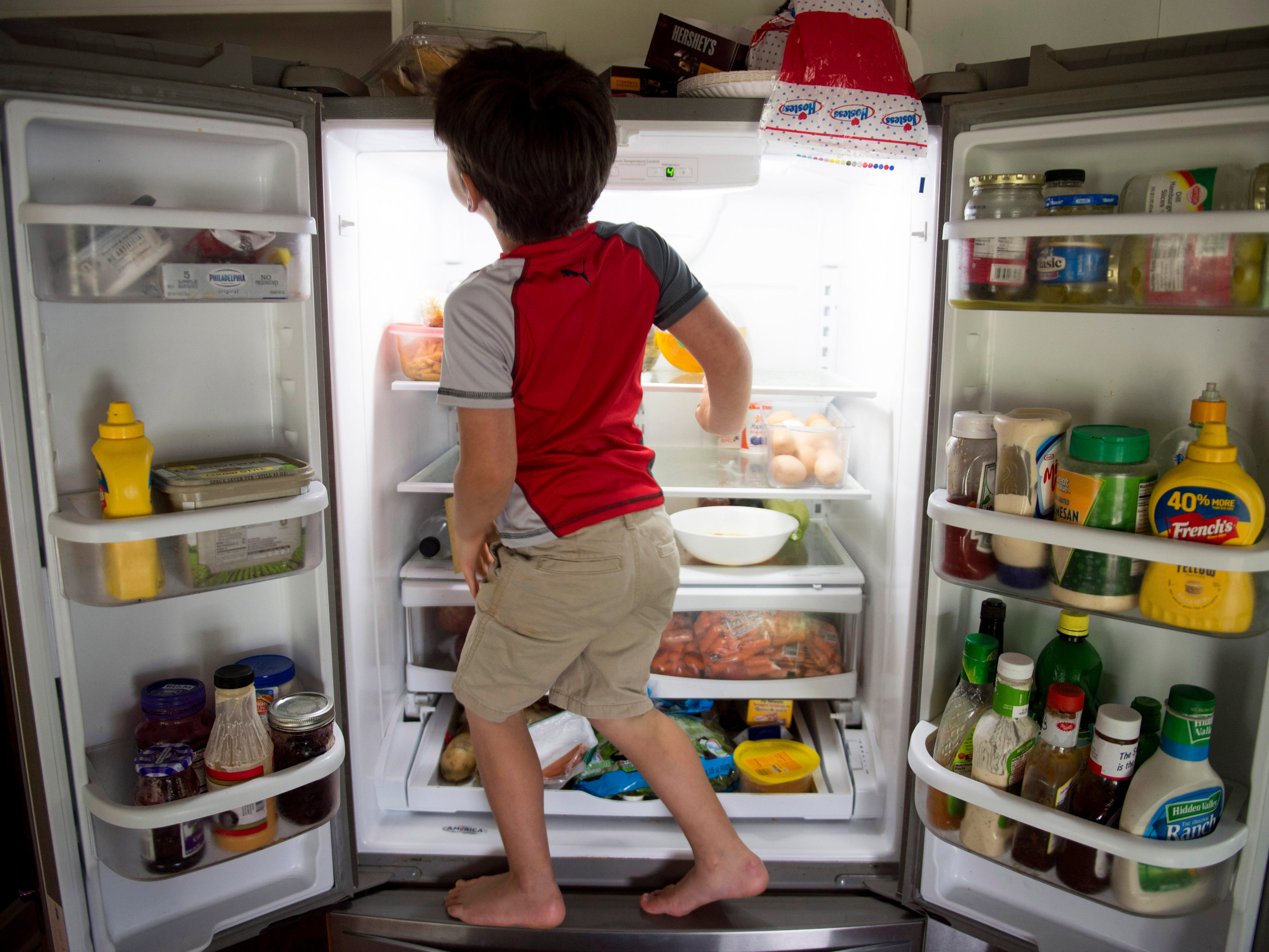 Leland Smith, 5, offers his services to retrieve something from his great aunt's refrigerator for his mom, Amanda in June of 2017. Amanda Smith uses a motorized wheelchair which makes it difficult to reach items on top of the appliance.
