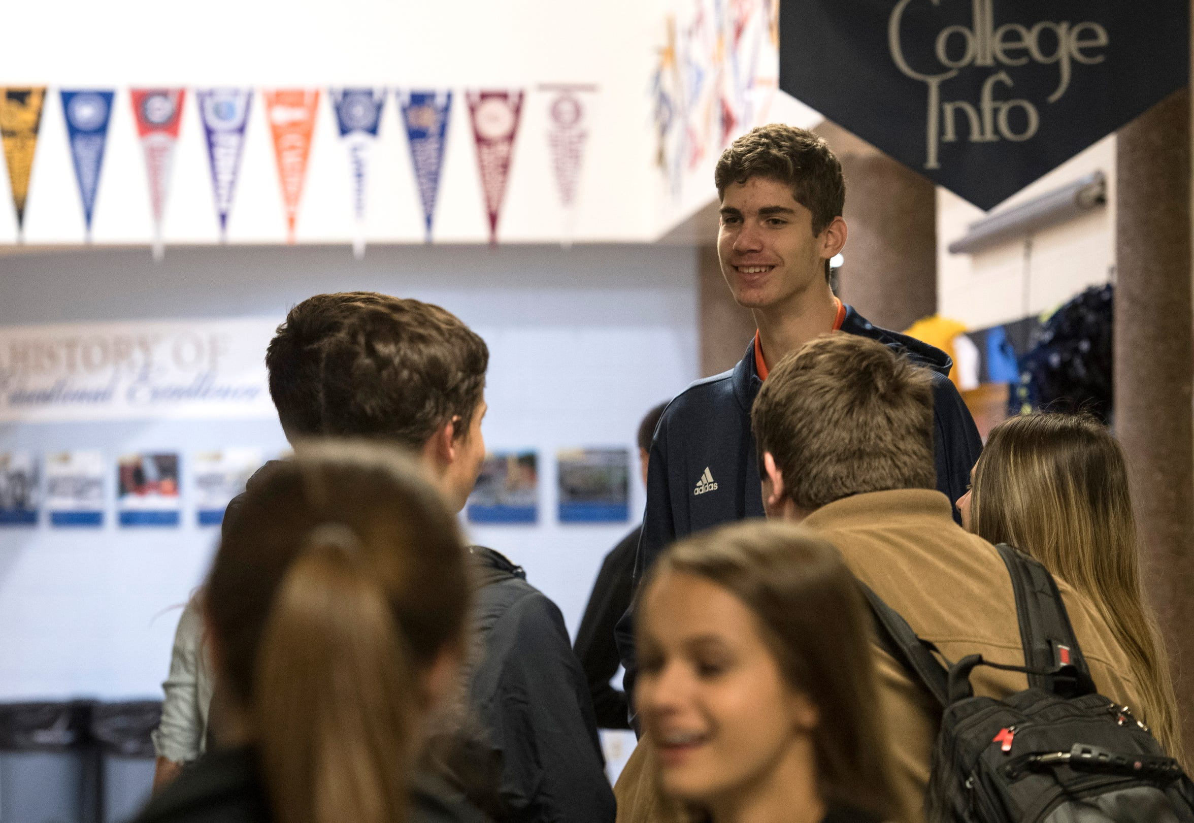 Noah Hupmann stands above the crowd as he chats with his peers while on a break between classes at Evansville Day School Wednesday, Nov. 14, 2018.