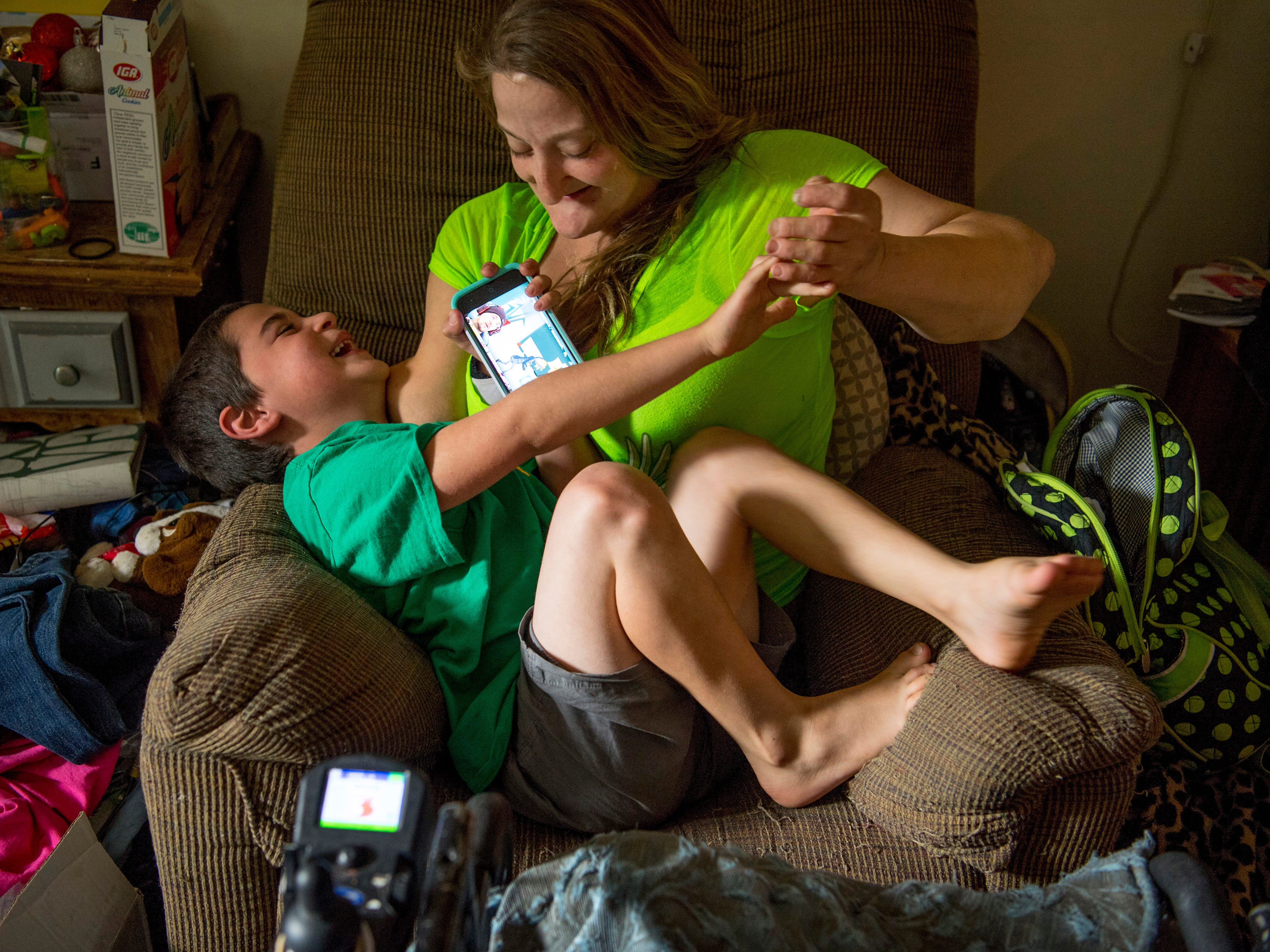 A tickle fight breaks out between Leland, 6, and Amanda as he tries to watch videos on her cell phone.