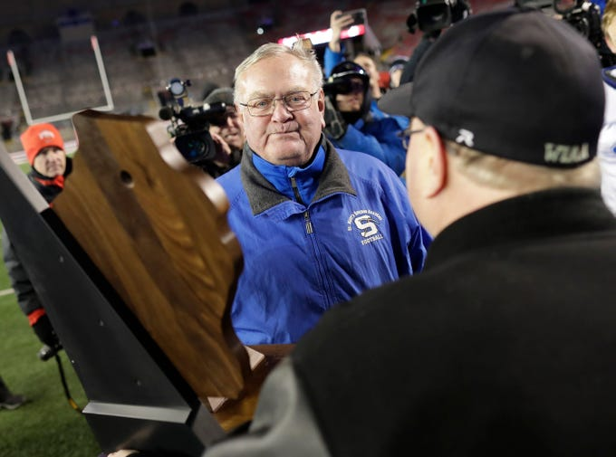 St. Mary's Springs Academy head coach Bob Hyland accepts the championship trophy after the Ledgers defeated Stratford High School during the WIAA Division  5 state championship football game on Thursday, November 15, 2018, at Camp Randall in Madison, Wis.