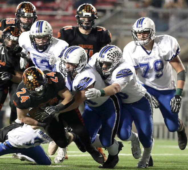 Stratford's Kade Ehrike is brought down by a swarm of St. Mary's Springs defenders during the WIAA Division  5 state championship game Thursday at Camp Randall Stadium in Madison.