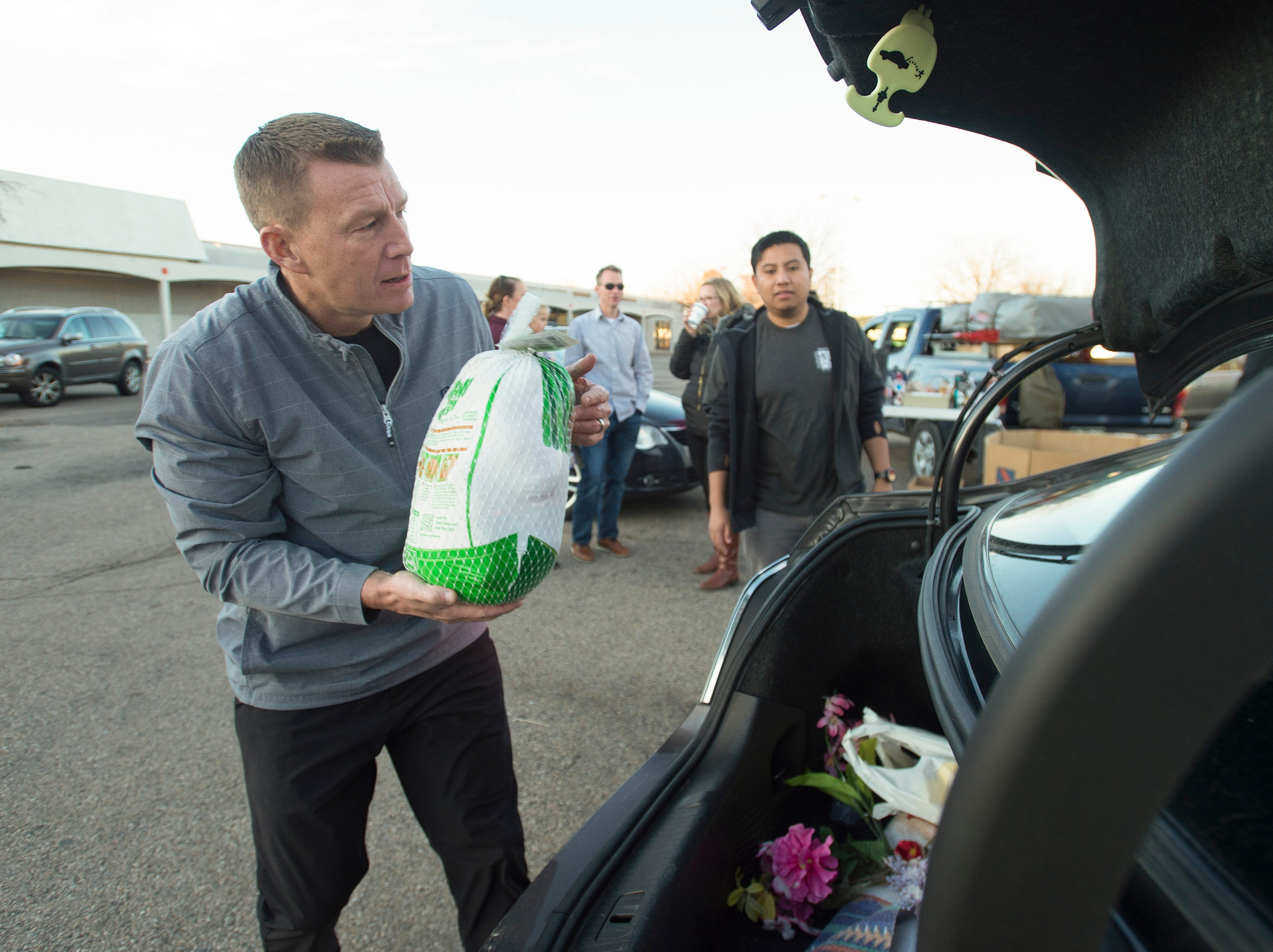 Volunteer Keith VanTassell collects a donated turkey as people drop off turkeys for Thanksgiving during the Food Bank for Larimer County's Stuff The Truck Turkey Donation on Thursday, November 15, 2018.