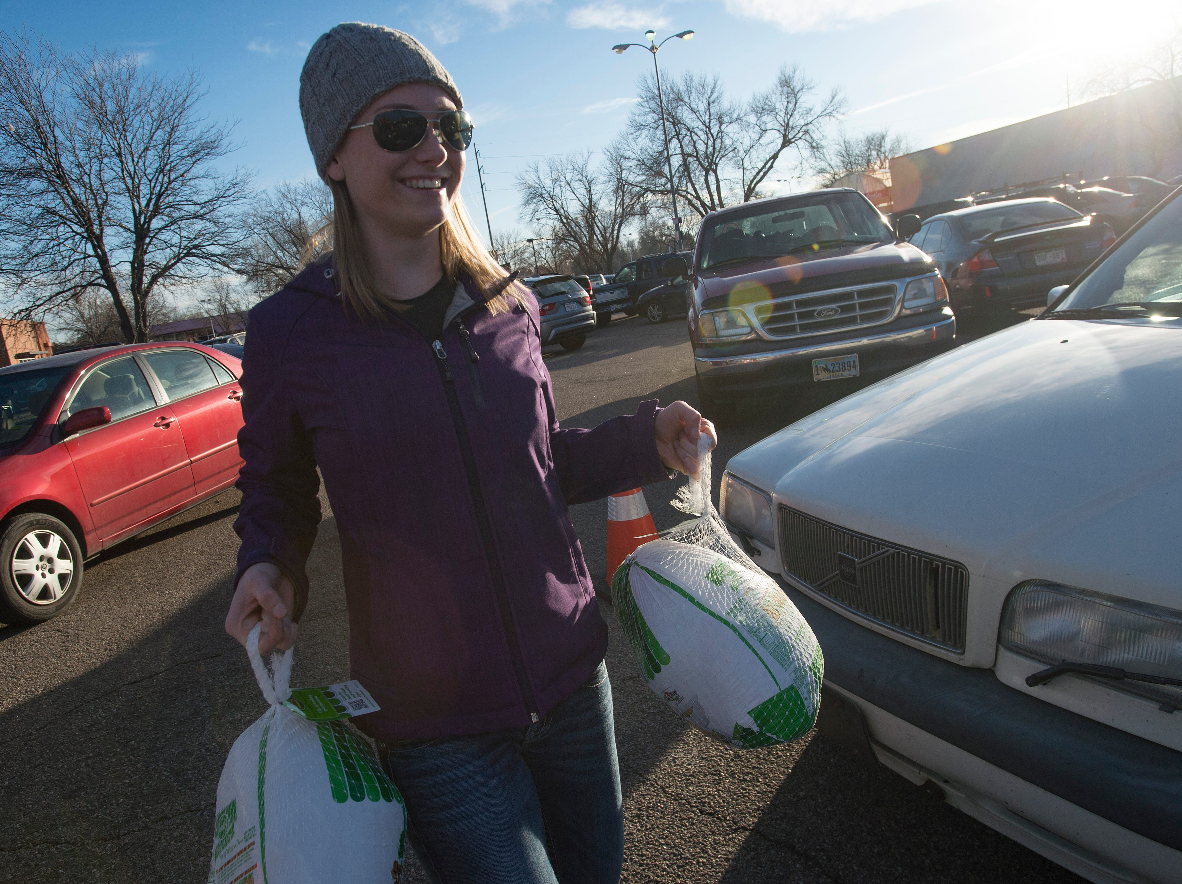 Volunteer Kylie Jaramillo collects donated turkeys during the Food Bank for Larimer County's Stuff The Truck Turkey Donation on Thursday, November 15, 2018.