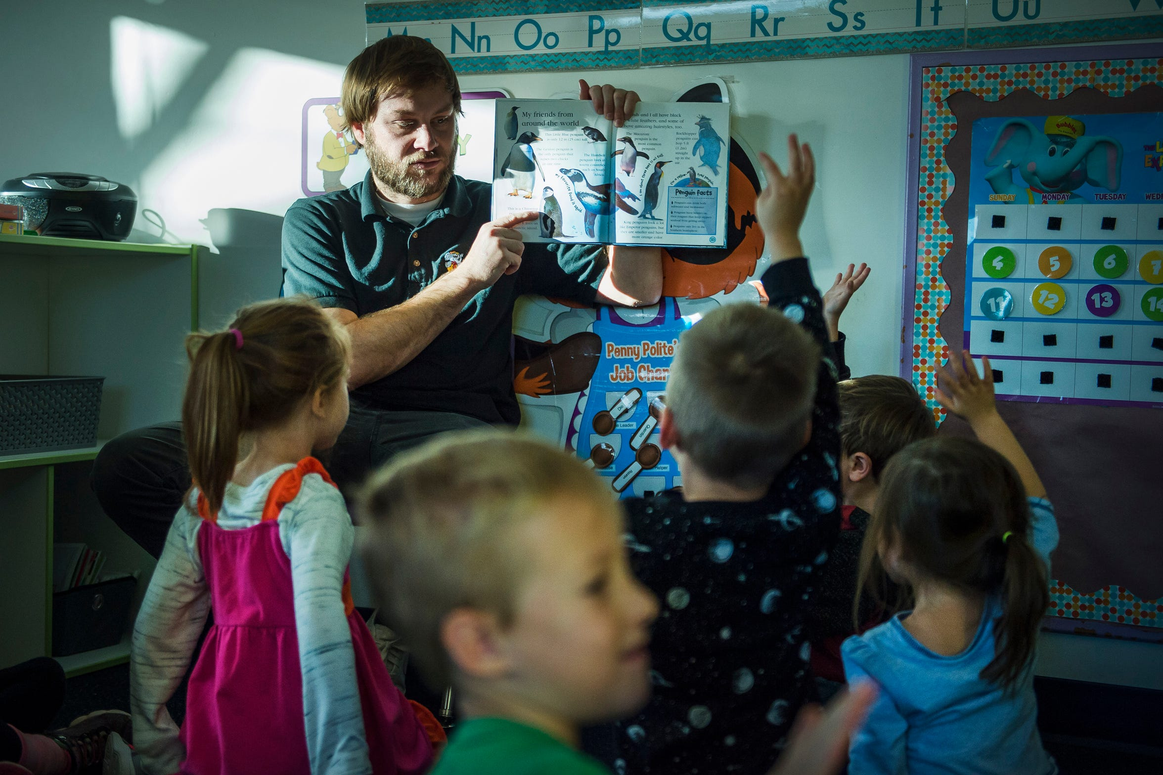"Pre-K teacher Christopher Smith asks his class which penguin they would want to be after reading the class ""Watch Me Grow: Penguin"" by Lisa Magloff on Thursday, Nov. 15, 2018, at The Learning Experience child development center in Fort Collins, Colo."