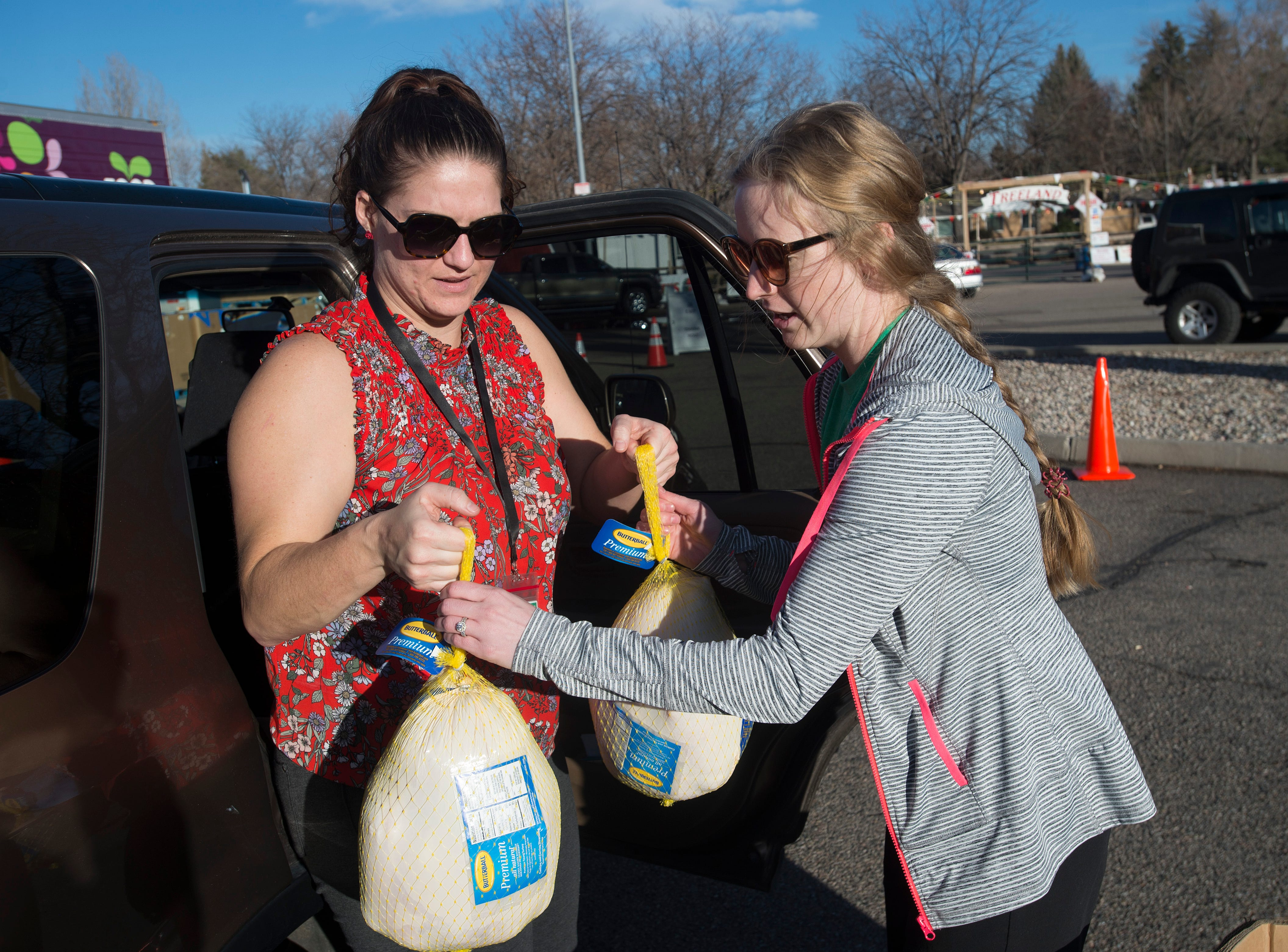 Volunteer Alicia Cooley, right, collects a pair of the 21 donated turkeys dropped off by Leigh Luxen during the Food Bank for Larimer County's Stuff The Truck Turkey Donation on Thursday, November 15, 2018.