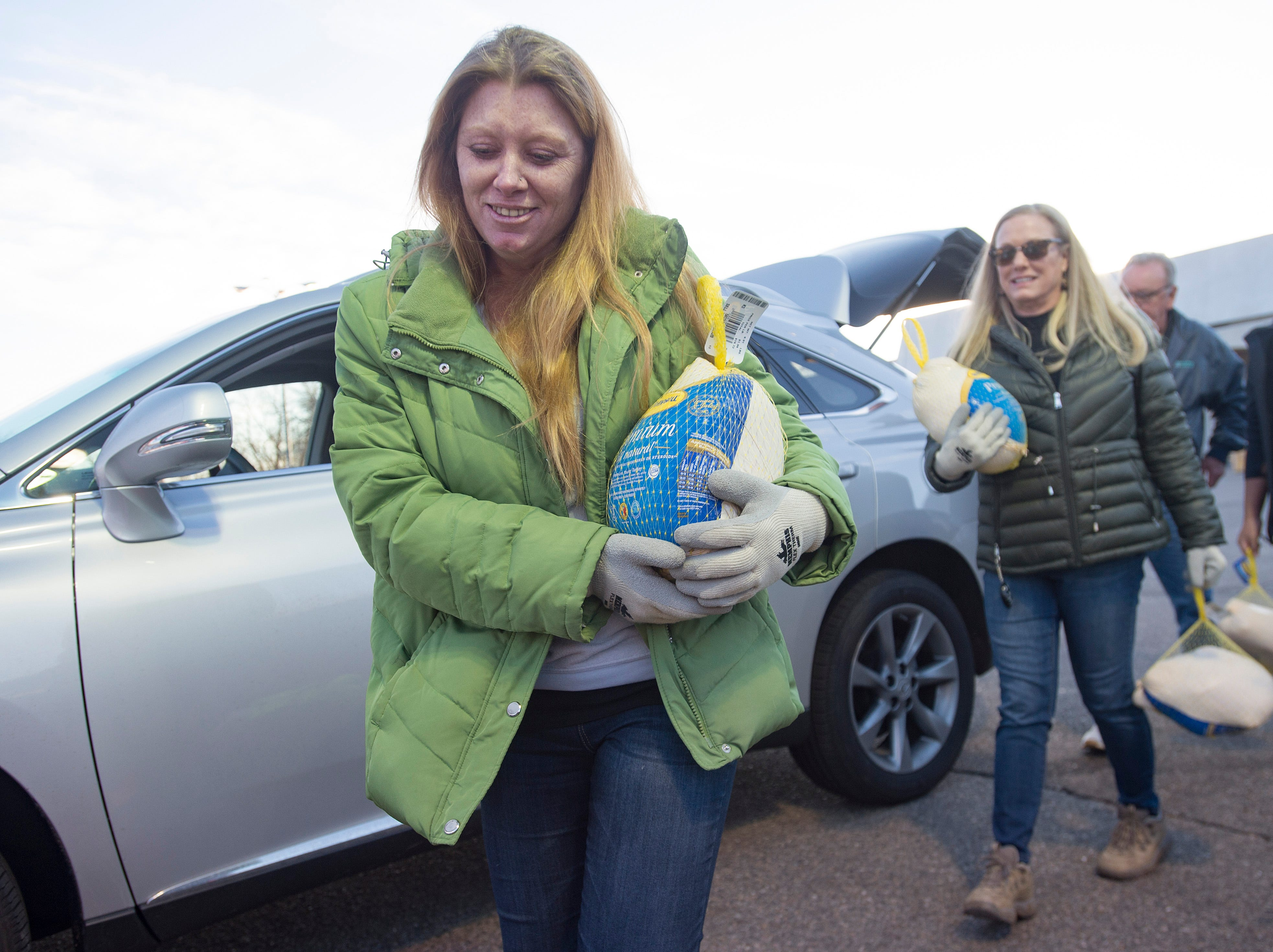 Volunteer Tori DuChateau, left, carries a donated turkey as people drop off turkeys for Thanksgiving during the Food Bank for Larimer County's Stuff The Truck Turkey Donation on Thursday, November 15, 2018.
