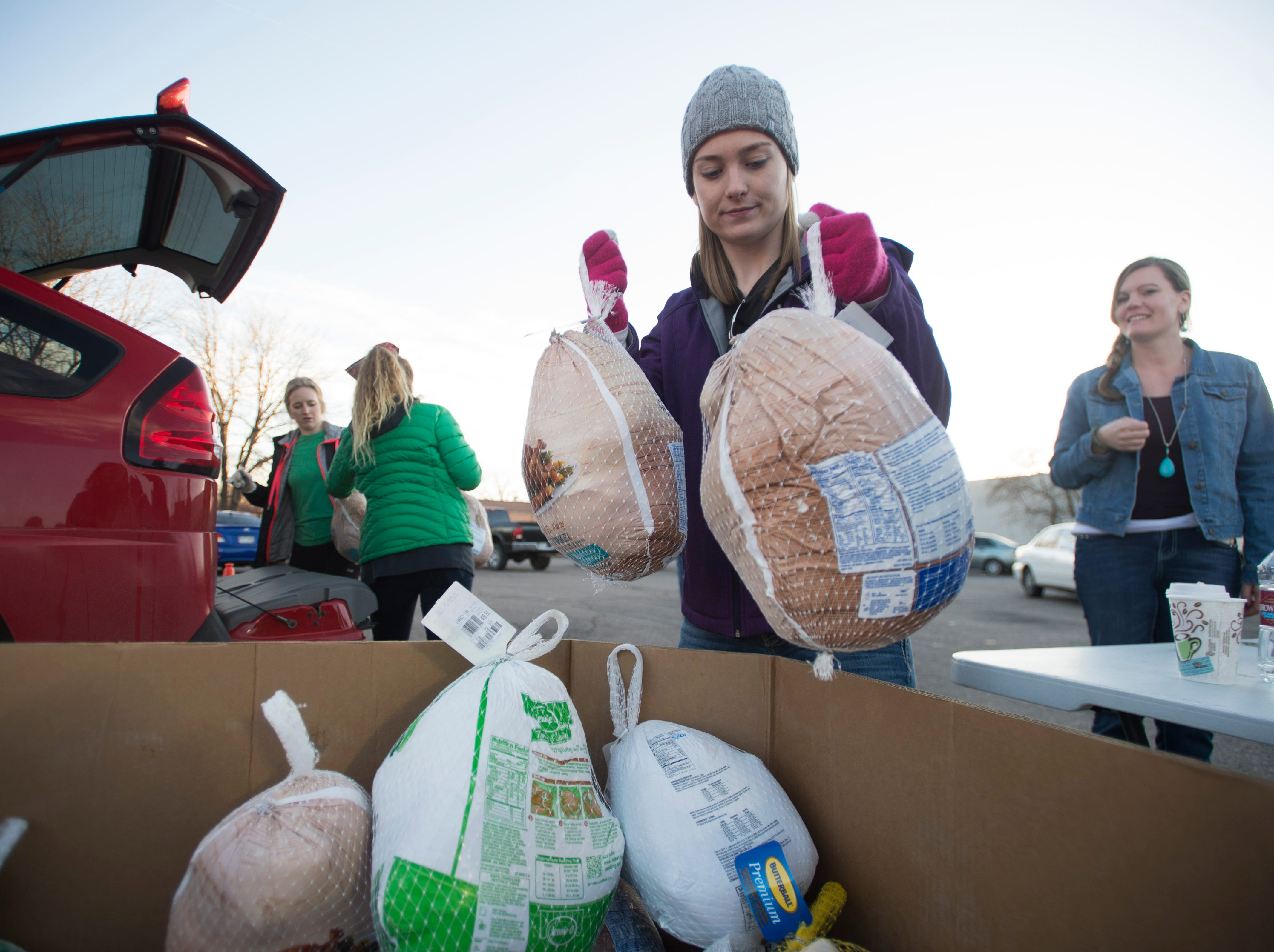 Volunteer Kylie Jaramillo drops donated turkeys into a bin during the Food Bank for Larimer County's Stuff The Truck Turkey Donation on Thursday, November 15, 2018.
