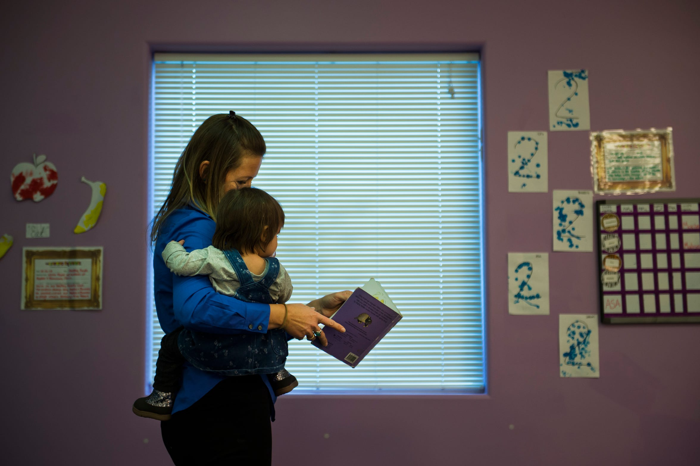 The Learning Experience owner and business manager Sara Brownell reads to one-year-old Marilyn Duran on Thursday, Nov. 15, 2018, at The Learning Experience child development center in Fort Collins, Colo.