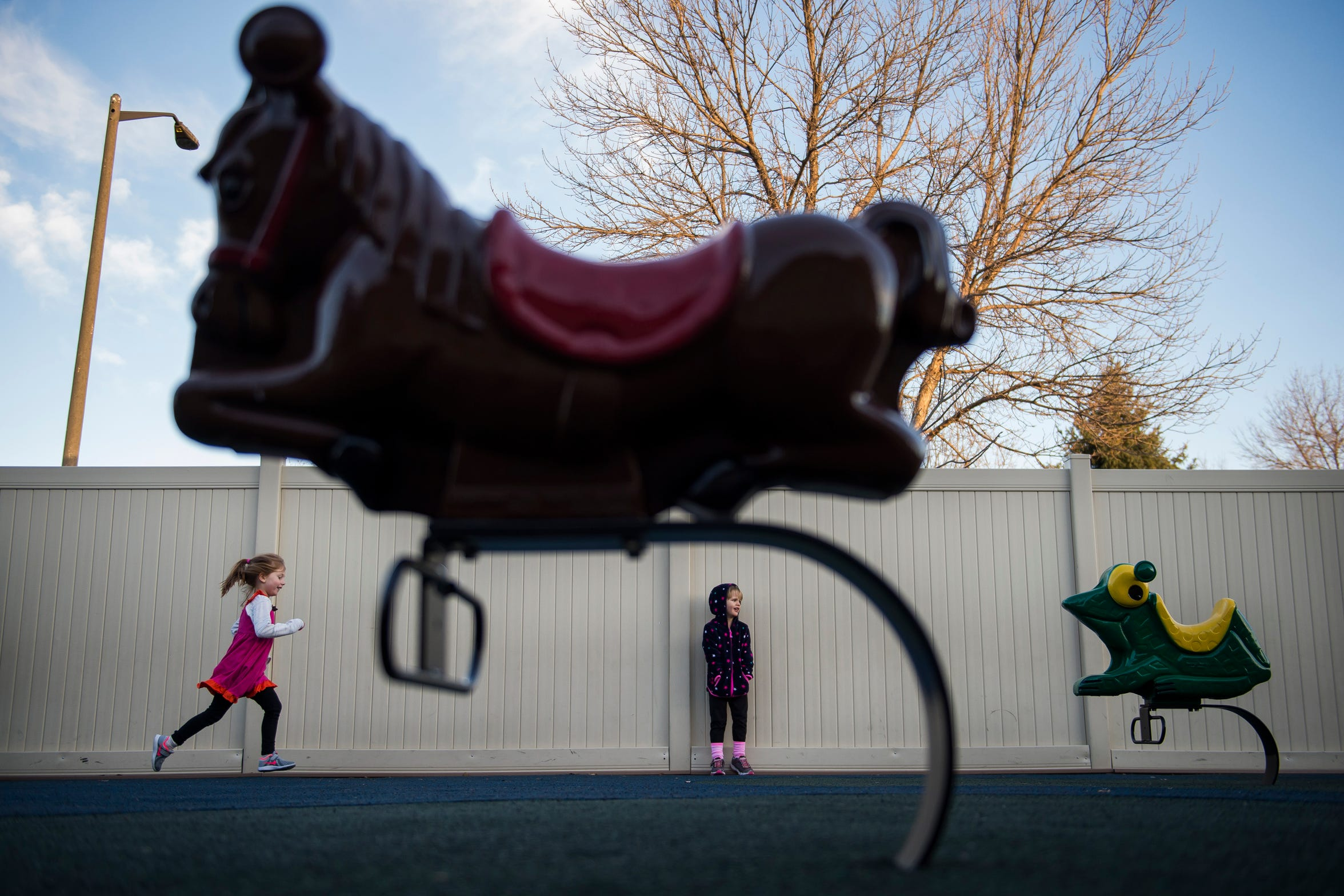 Scarlett Archer, 4, runs through the playground area while Roz Nitchie-Shonka, 4, looks on during a recess time on Thursday, Nov. 15, 2018, at The Learning Experience child development center in Fort Collins, Colo.