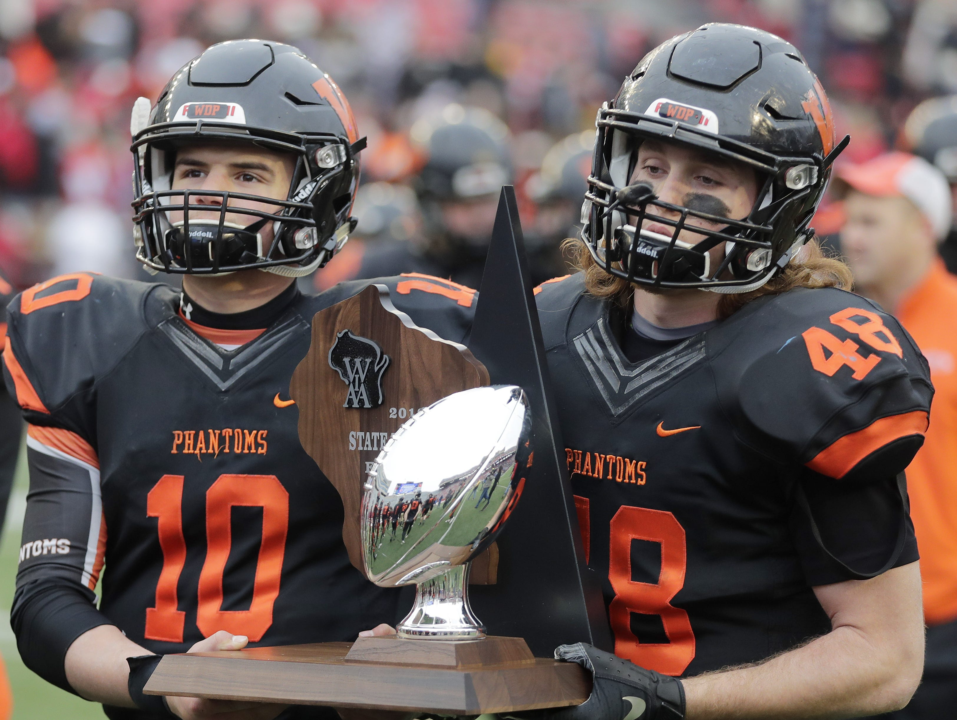 West De Pere's Josh Blount (10) and Matt Kempen (48) carry the runners up trophy after the Phantoms lost to Catholic Memorial in the WIAA Division 3 championship game at Camp Randall Stadium on Friday, November 16, 2018 in Madison, Wis.