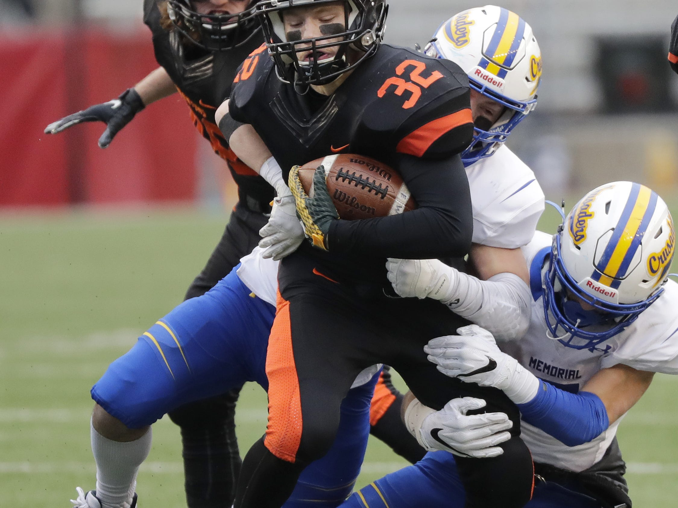 West De Pere's Evan Frisque (32) is tackled against Catholic Memorial in the WIAA Division 3 championship game at Camp Randall Stadium on Friday, November 16, 2018 in Madison, Wis.