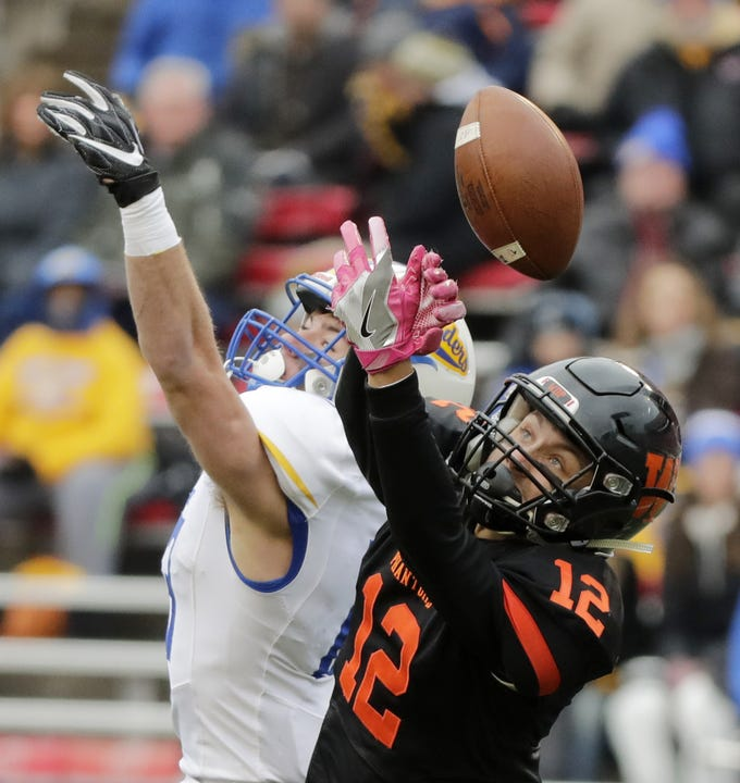 West De Pere's John Edinger (12) defends a pass intended for Catholic Memorial's Tate Kopulos (13) in the WIAA Division 3 championship game at Camp Randall Stadium on Friday, November 16, 2018 in Madison, Wis.