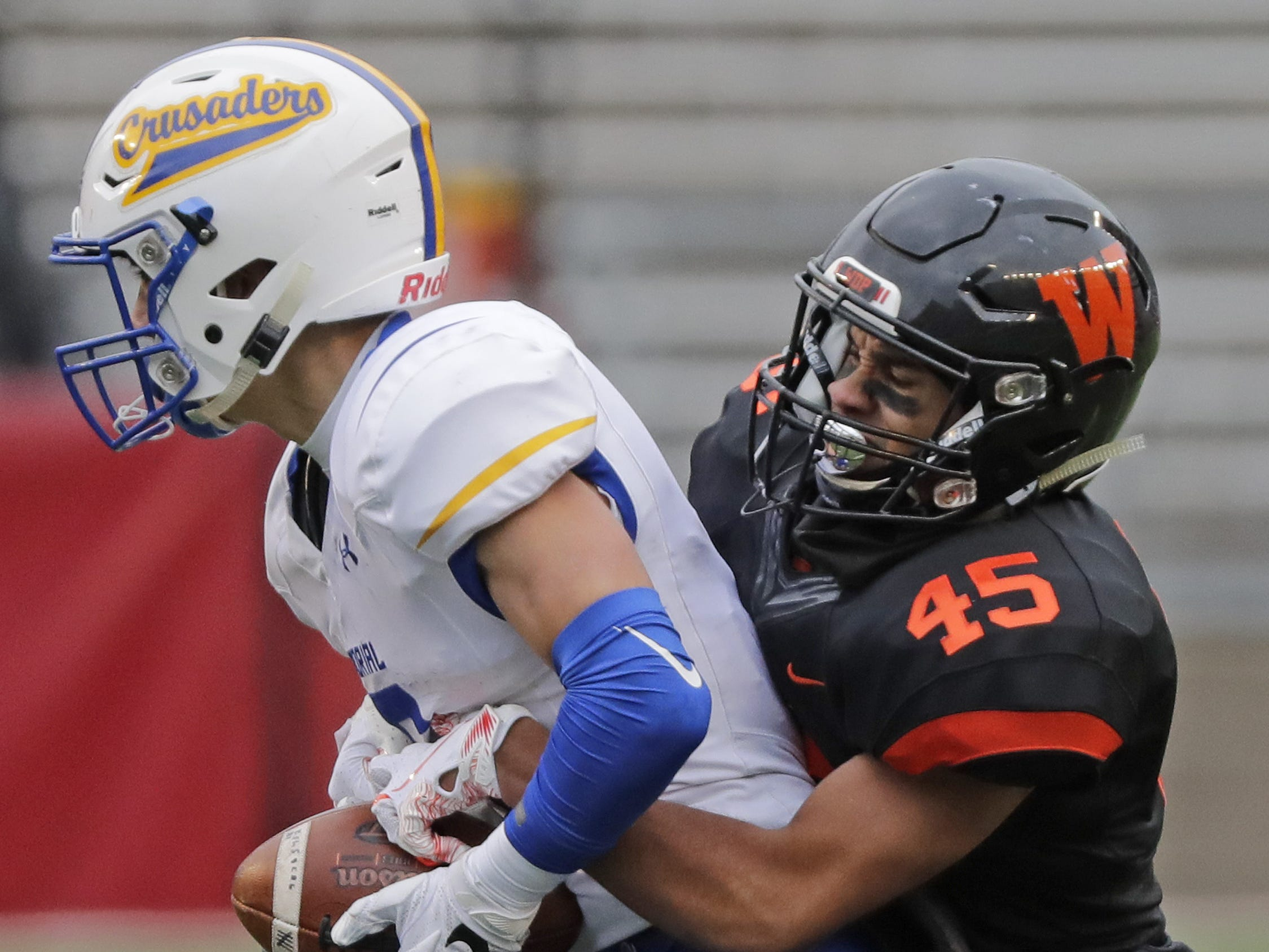 West De Pere's Isiah Burdette (45) causes a fumble by Catholic Memorial's Joe Sikma (6) in the WIAA Division 3 championship game at Camp Randall Stadium on Friday, November 16, 2018 in Madison, Wis.