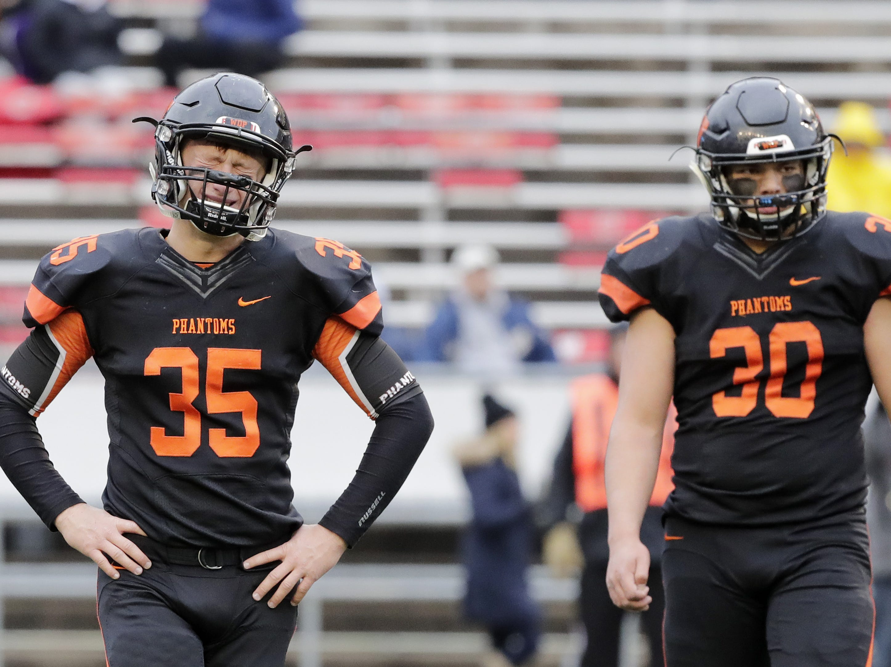 West De Pere's Alex Spitzer (35) and Cody Cavil (30) leave the field after the Phantoms lost to Catholic Memorial in the WIAA Division 3 championship game at Camp Randall Stadium on Friday, November 16, 2018 in Madison, Wis.