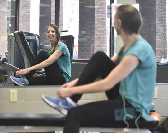 Kayla Wilke of Sturgeon Bay ties her work-out shoes in front of a mirror at the Door County YMCA in Sturgeon Bay. She said it is her favorite place to be.