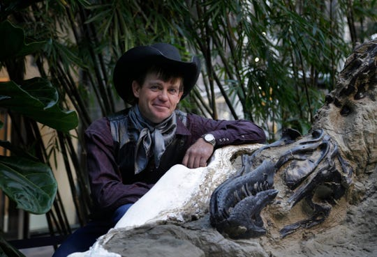 """In this Nov. 14, 2013 photo, Clayton Phipps of Brusett, Mont., poses for a picture with one of the two """"dueling dinosaurs"""" he discovered on a Montana ranch in 2006. Ownership of the fossils are the subject of a legal battle over whether they are part of a property's surface rights or mineral rights. The nearly complete skeletons were put up for auction in New York in 2013, but bidding topped out at $5.5 million, failing to meet the reserve price."""