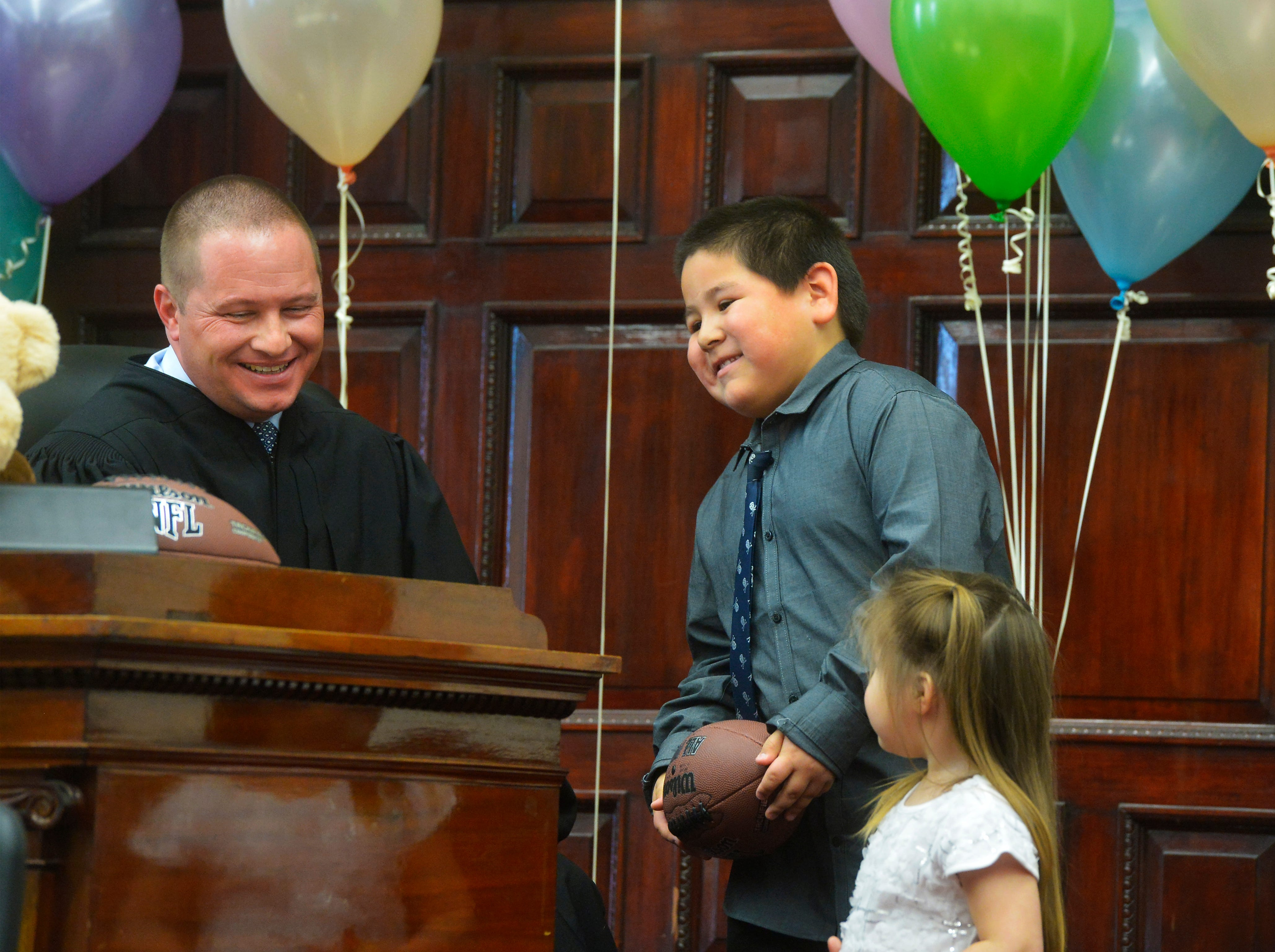 Anthony Morsette-Nava, age 7, and his sister Lexi, age 3, visit with Judge Greg Pinski at the judge's bench after he finalized their adoption on Friday afternoon in the Cascade County Courthouse