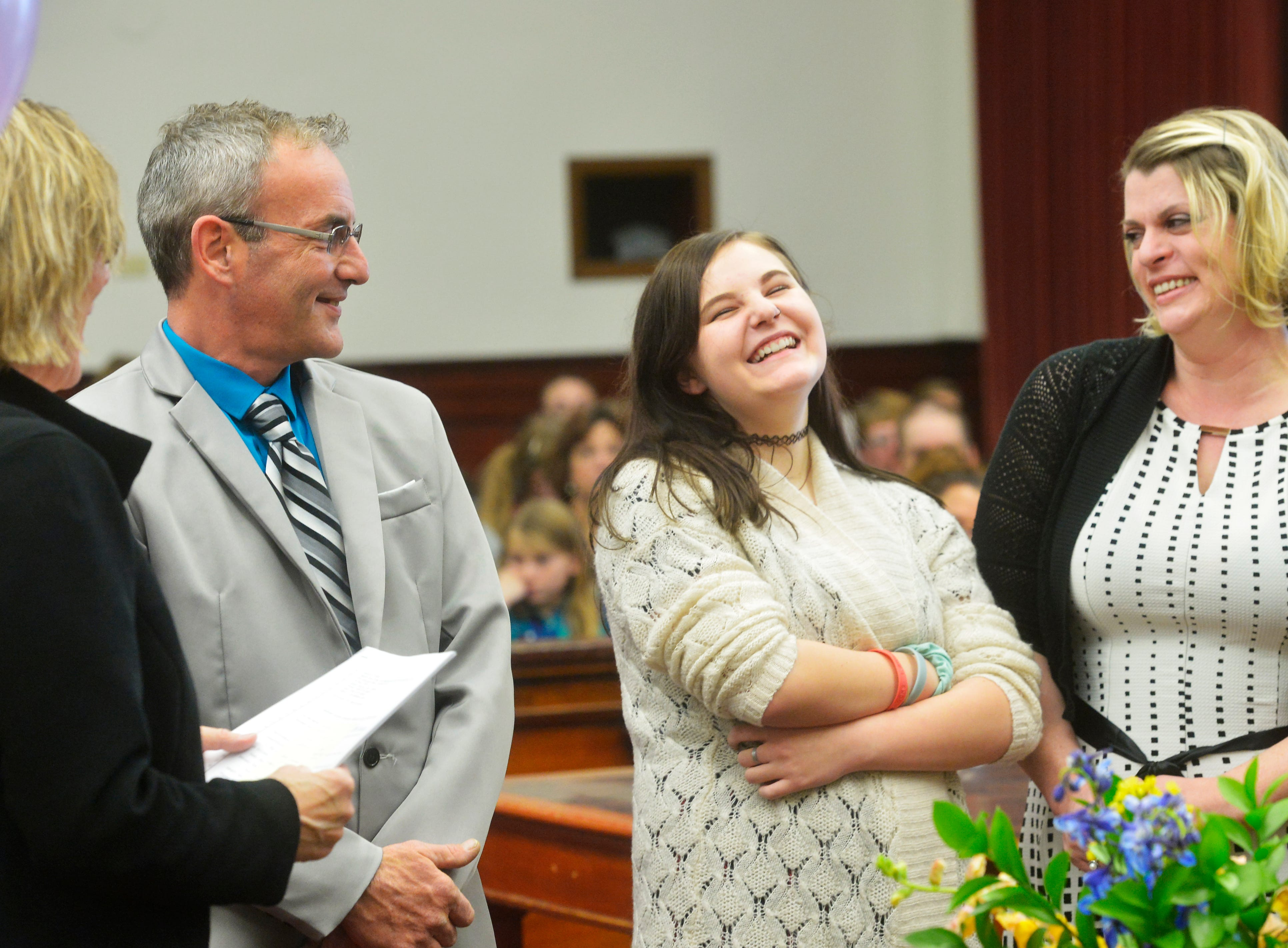 Patience DeRosa, age 13, laughs at a joke during her adoption ceremony as her adoptive parents, Jason and Hyasienth, look on in the Cascade County Courthouse on Friday.