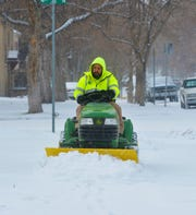 Mike Trotchie with Cascade County Public Works Department, clears snow from the sidewalks around the Cascade County Courthouse on Friday afternoon.