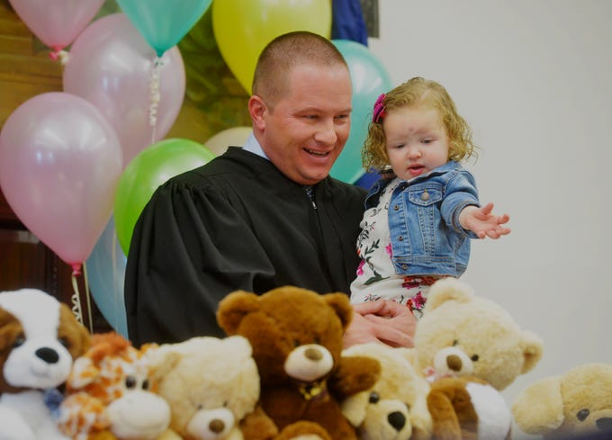 Judge Greg Pinski helps Everly Ogden pick a stuffed animal after he finalized her adoption by Justin and Amanda Ogden at Friday's adoption ceremony.