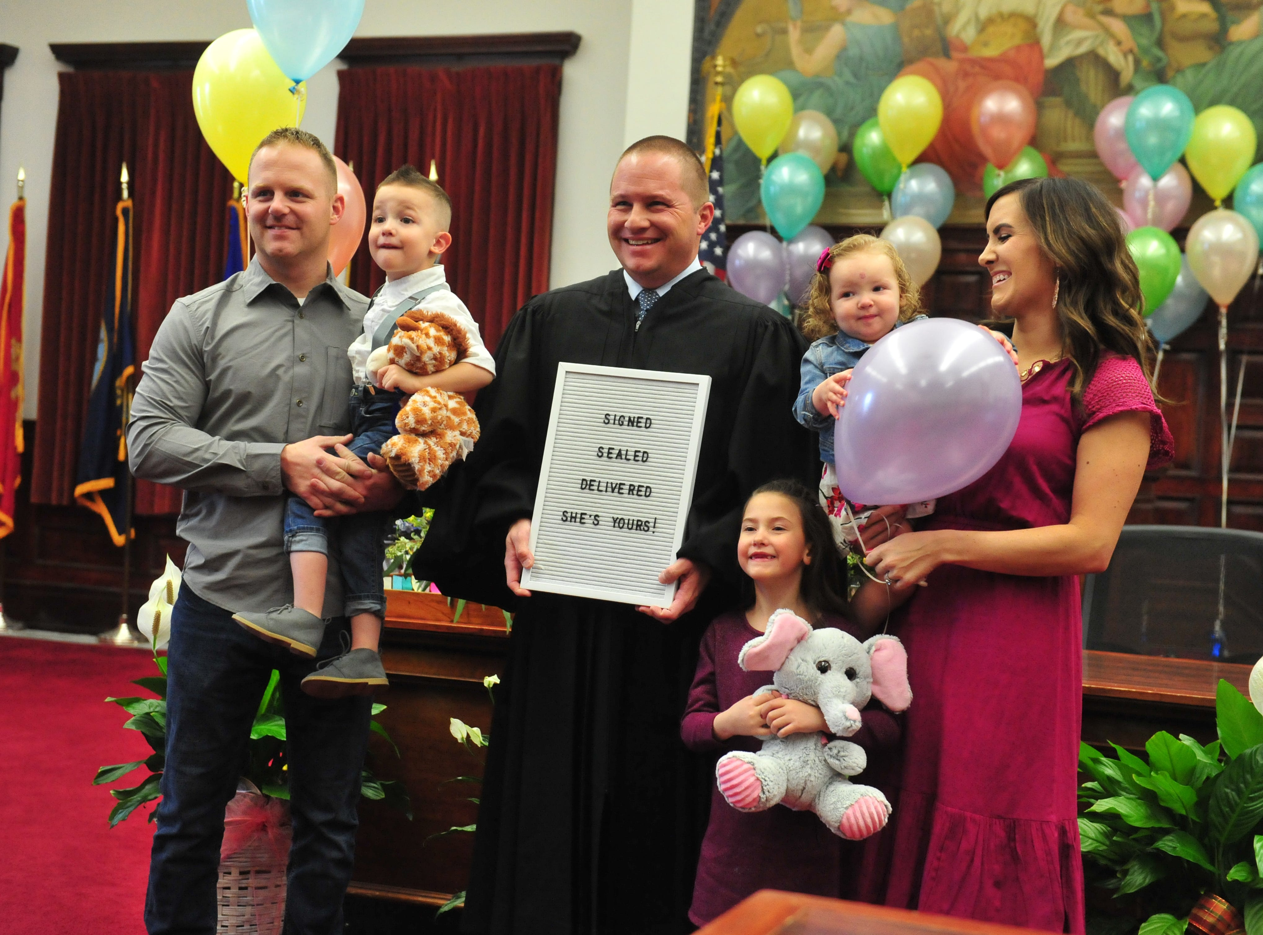 The Ogden family poses for photos with Judge Greg Pinski after the adoption of one-year-old Everly was finalized at the Great Falls Adoption Day celebration on Friday in the Cascade County Courthouse.