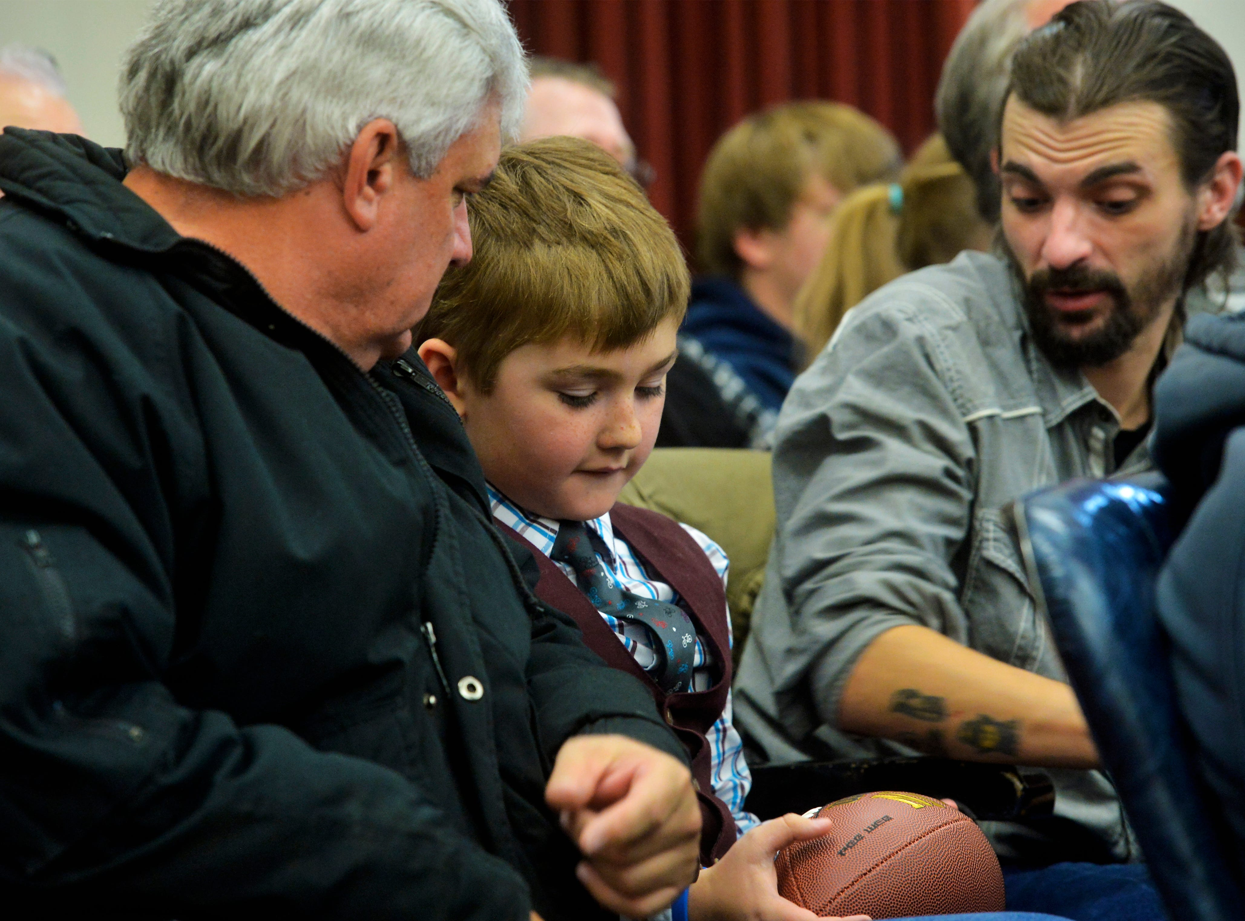 Mihkale Murphy, age 9, admires the gift football he received when his adoption was finalized at an adoption ceremony on Friday in the Cascade County Courthouse.