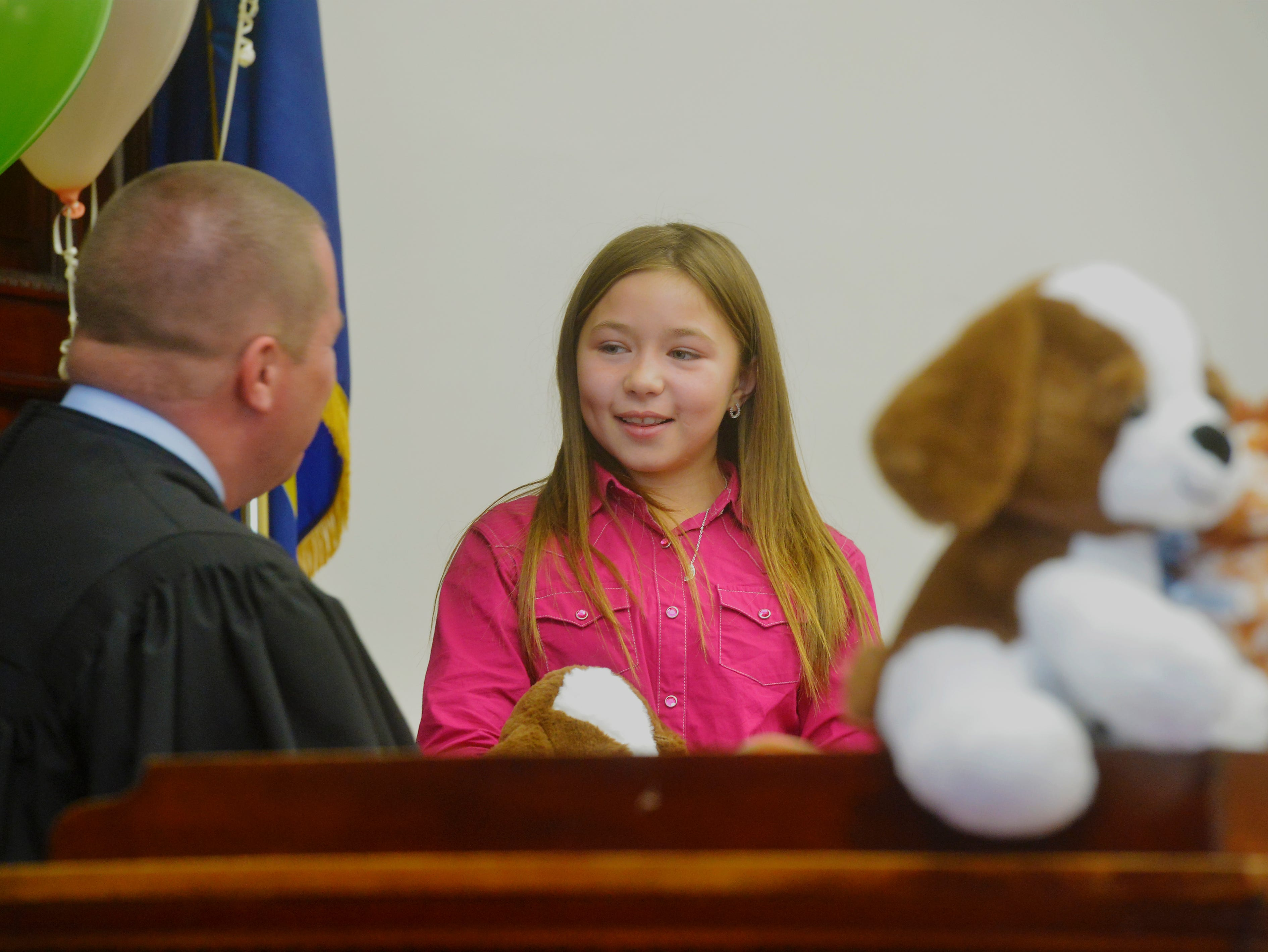 Nikki Hartwell, age 9, talks with judge Greg Pinski, who finalized her adoption by Kelly and Tasha Hartwell of Sweetgrass, Friday afternoon during the Great Falls Adoption Day celebration at the Cascade County Courthouse.