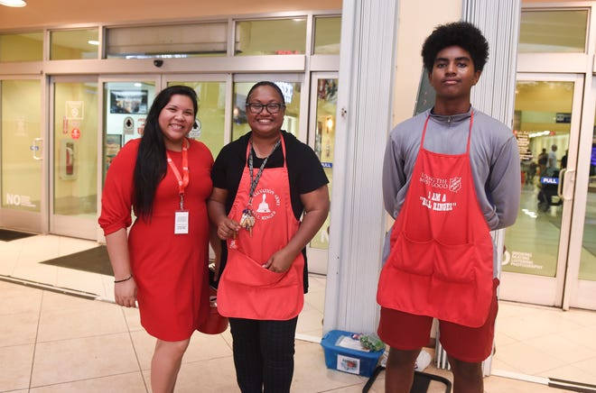 Amanda Blas, former senatorial candidate and executive director of the governor's Commission on Decolonization, left, Oyaol Ngirairikl director of communications for the Office of the Governor, and Dewayne Ngirairikl volunteer as bell-ringers for the Red Kettle Drive at Agana Shopping Center, Nov. 16, 2018.