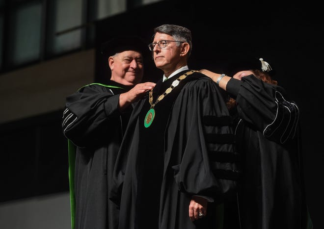 New University of Guam President Thomas W. Krise, center, receives the Medallion of Office during his investiture ceremony at the UOG Calvo Field House on Nov. 16, 2018.