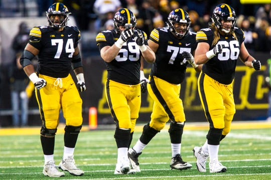 Iowa offensive lineman Tristan Wirfs (74) Ross Reynolds (59) Alaric Jackson (77) and Levi Paulsen (66) celebrate an overturned call against Northwestern. All but Reynolds return for the Hawkeyes in 2019.