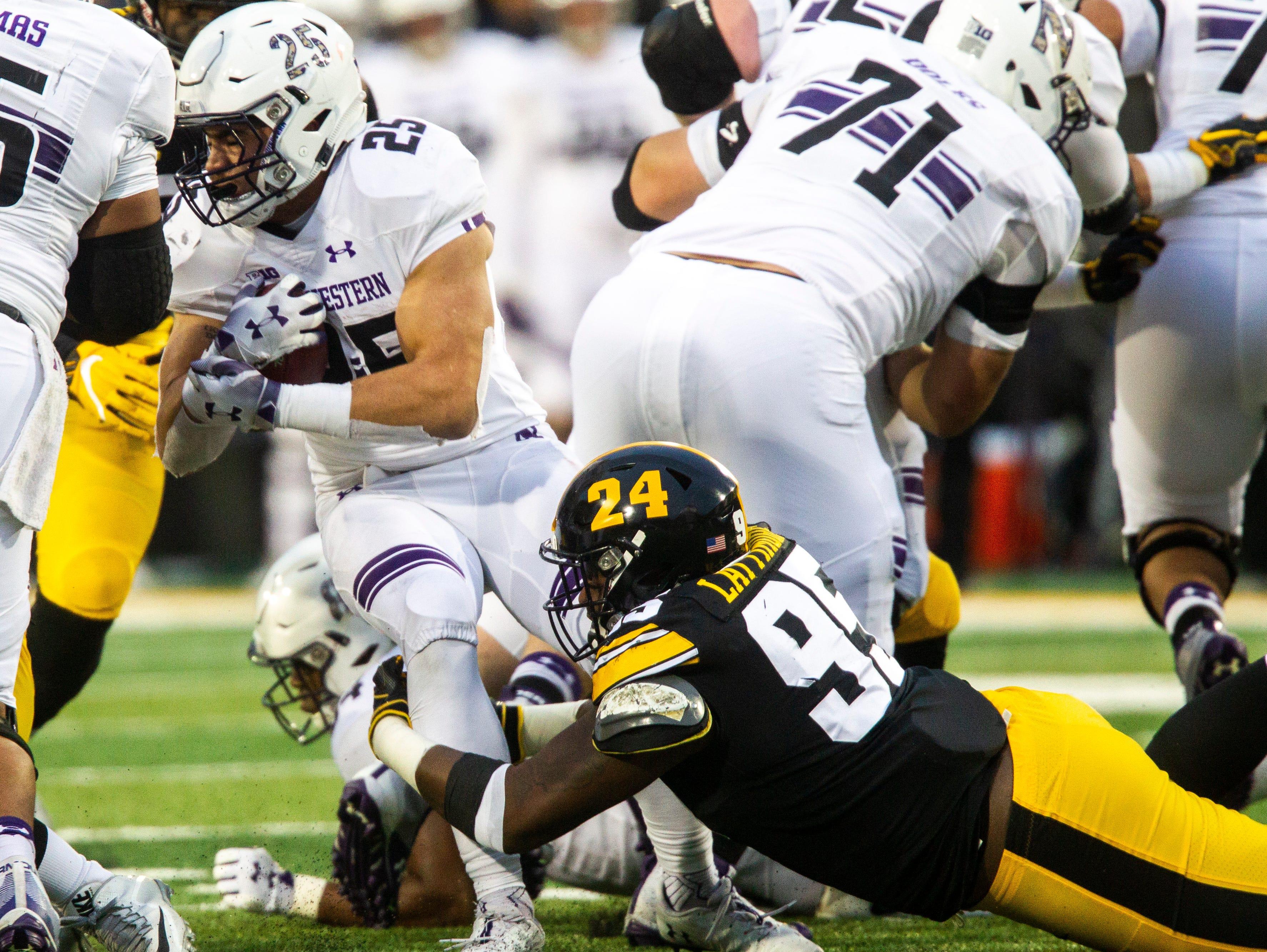 Iowa defensive lineman Cedrick Lattimore (95) tackles Northwestern's Isaiah Bowser (25) during a Big Ten Conference football game on Saturday, Nov. 10, 2018, at Kinnick Stadium in Iowa City.