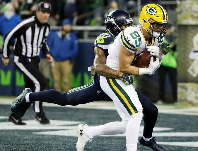 Green Bay Packers tight end Robert Tonyan (85) is tackled by Seattle Seahawks strong safety Bradley McDougald, left, after Tonyan caught a pass for a touchdown against the Seattle Seahawks during the first half of an NFL football game, Thursday, Nov. 15, 2018, in Seattle.