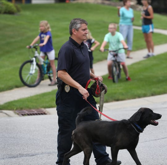 Todd Jordan walks Bear up to the Zionsville home of Subway spokesperson Jared Fogle in the 4500 block of Woods Edge Drive in the Austin Oaks subdivision where law enforcement, including the FBI, Indiana State Police and U.S. Postal Inspection Policeconducted a morning-long investigation at Fogle's home on Tuesday morning, July 7, 2015.