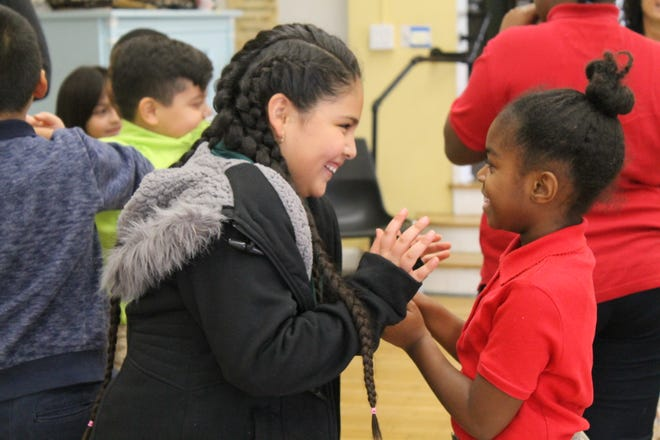 Anahi Medina, left, and Genesis Bradley, right, both third graders at Clarence Farrington School 61, play a game in which they demonstrate kind actions during a lesson about conflict resolution.